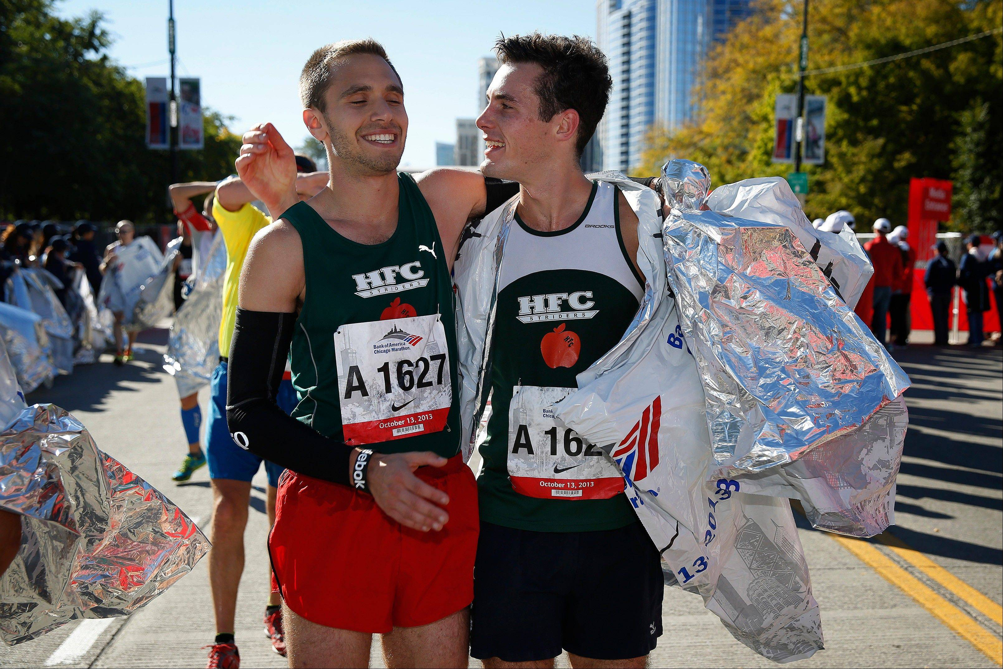 Andrew Holmes, left, of Newton, Mass., and Peter Ryan, right, of Holden, Mass., celebrate after finishing the Chicago Marathon on Sunday, Oct. 13, 2013, in Chicago.
