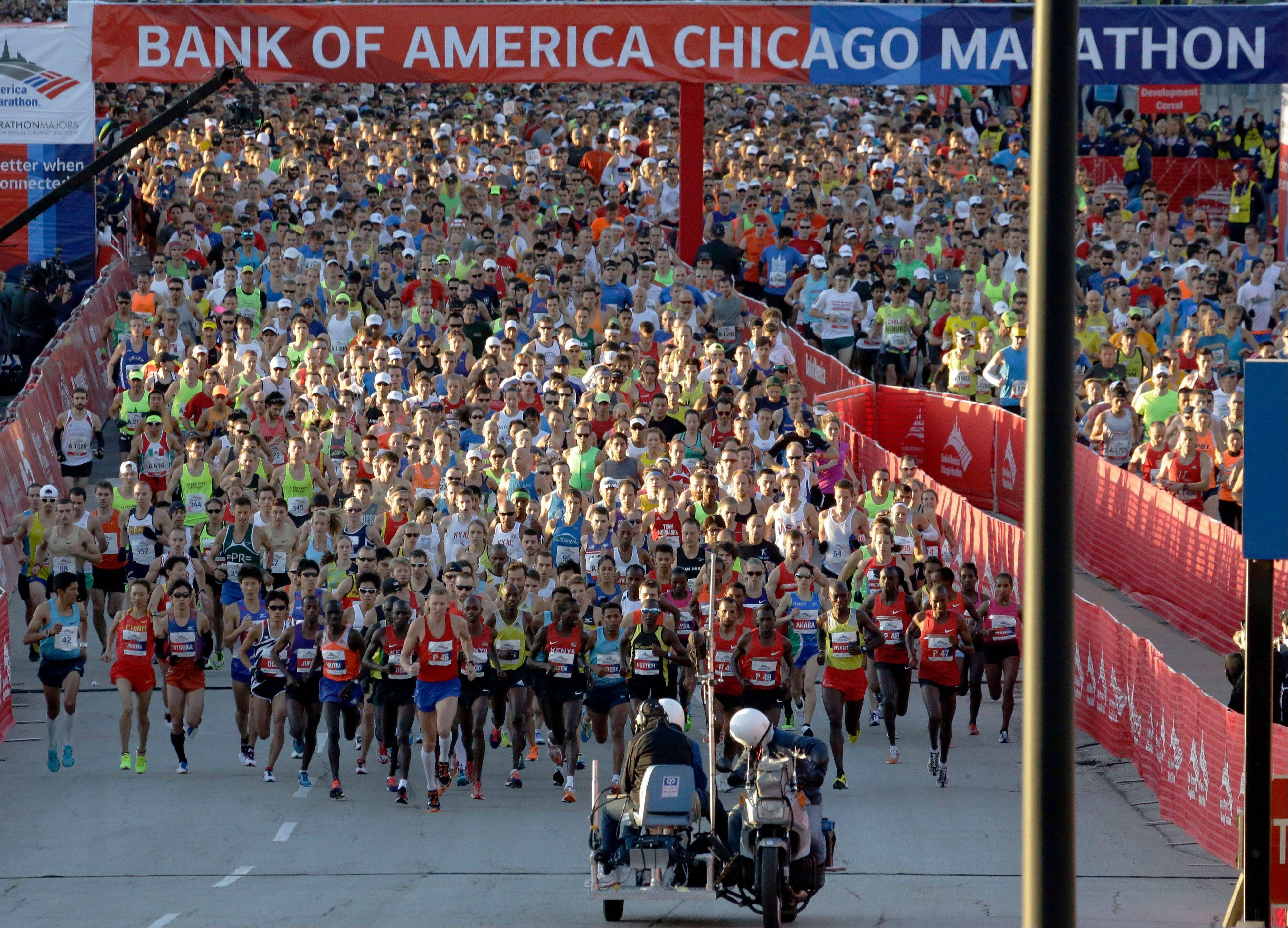 Runners start the Chicago Marathon in Chicago, Sunday, Oct. 13, 2013, nearly six months after the Boston Marathon bombings, with more police officers lining race routes and spectator areas.