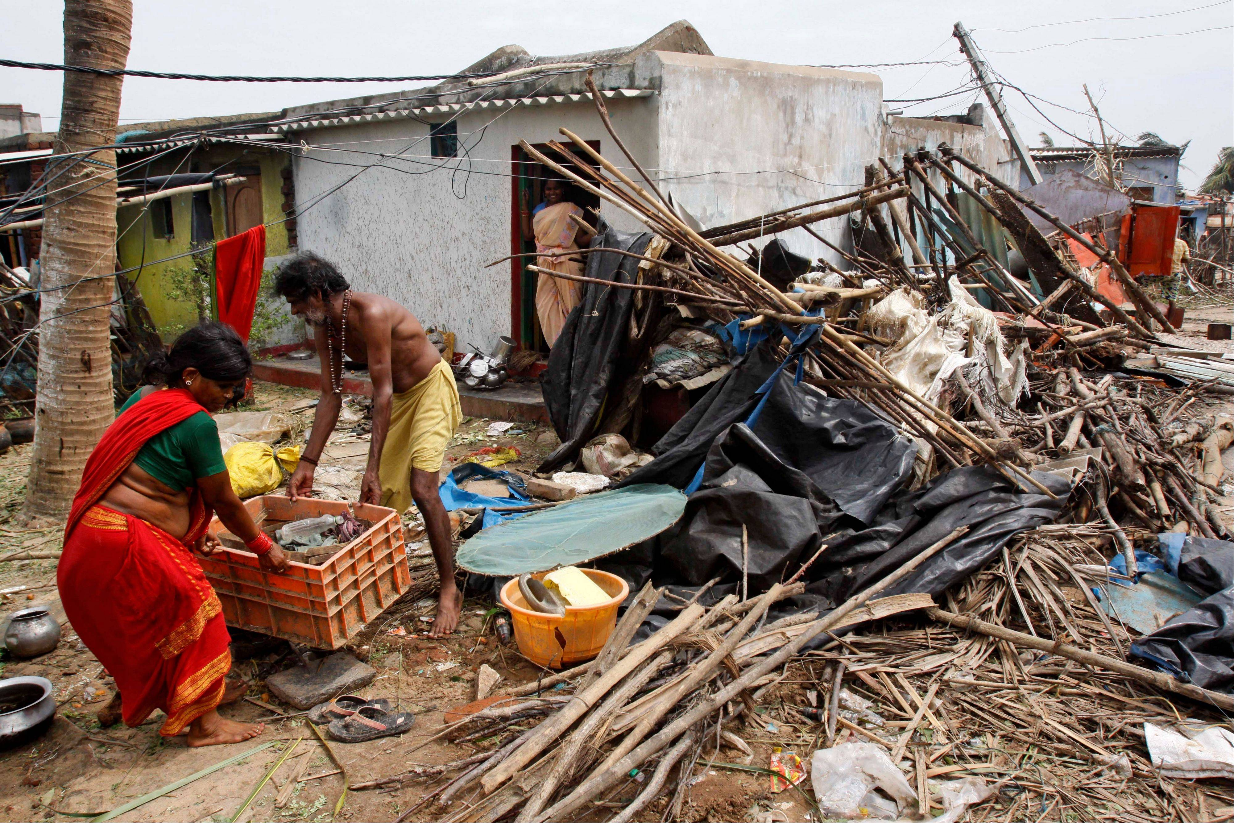 Indian villagers collect their belongings Sunday after the cyclone hit Arjipalli on the Bay of Bengal coast.