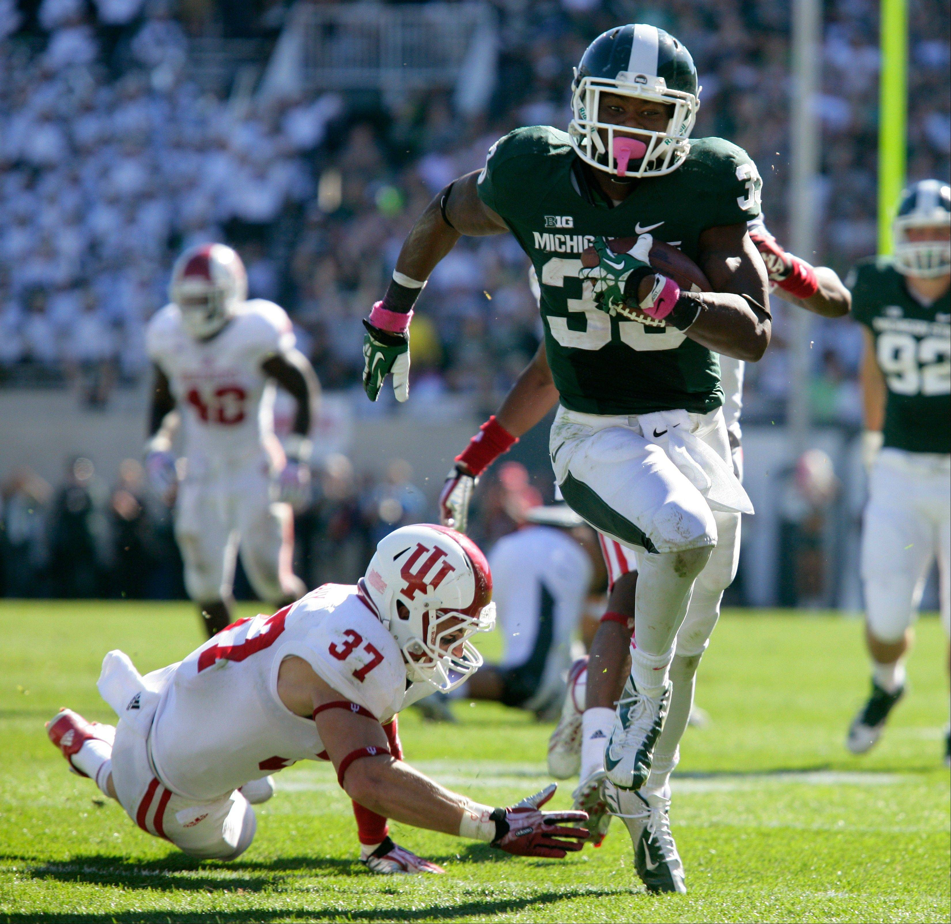 Michigan State's Jeremy Langford runs past Indiana's Mark Murphy for a 32-yard touchdown during the third quarter of Saturday's game in East Lansing, Mich. The Spartans won 42-28.