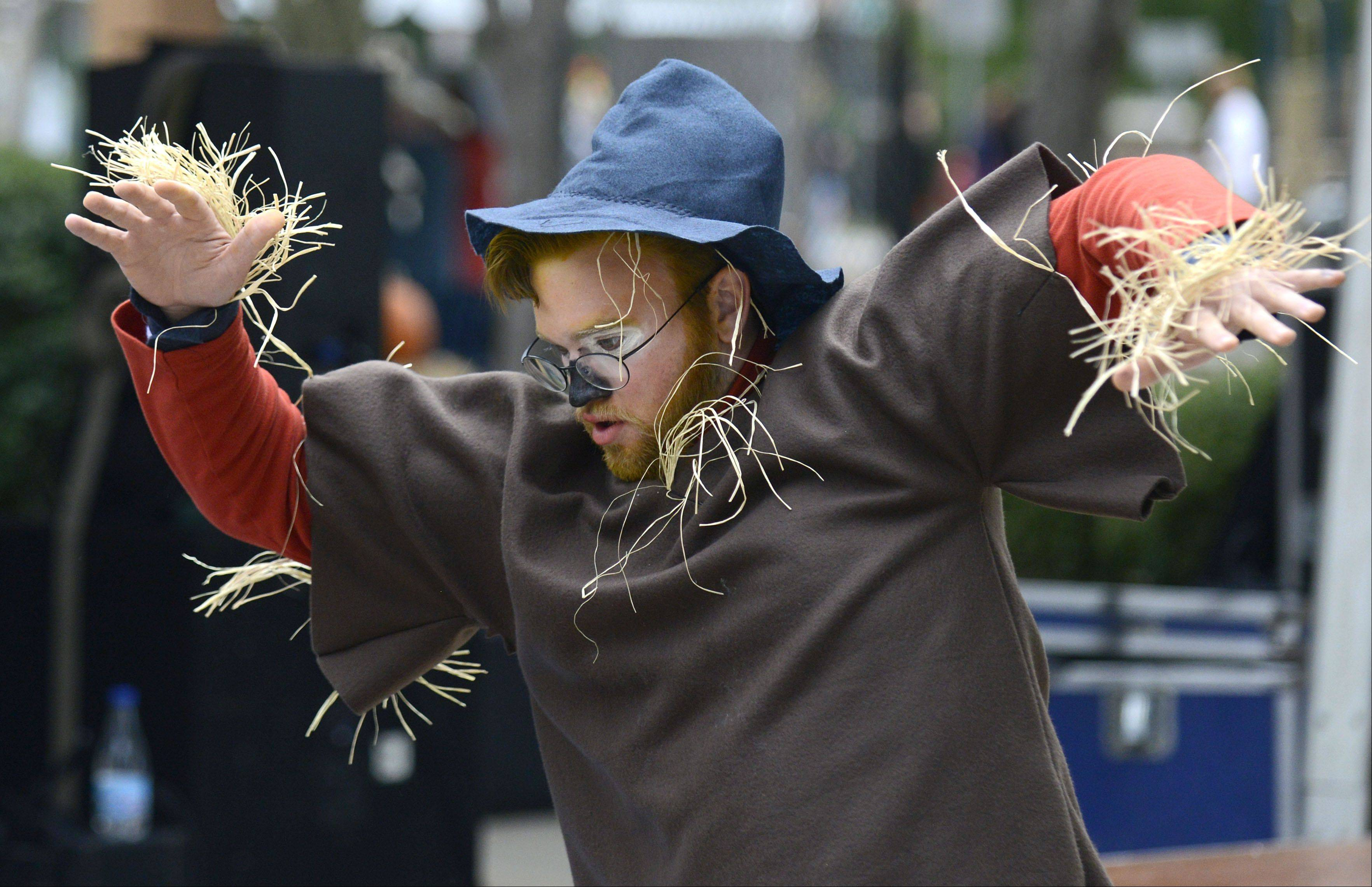 Steven Sledzinski, of Geneva, dressed as Chuck the Scarecrow Fest mascot, dances to live music in the square at Lincoln Park in St. Charles on Saturday.