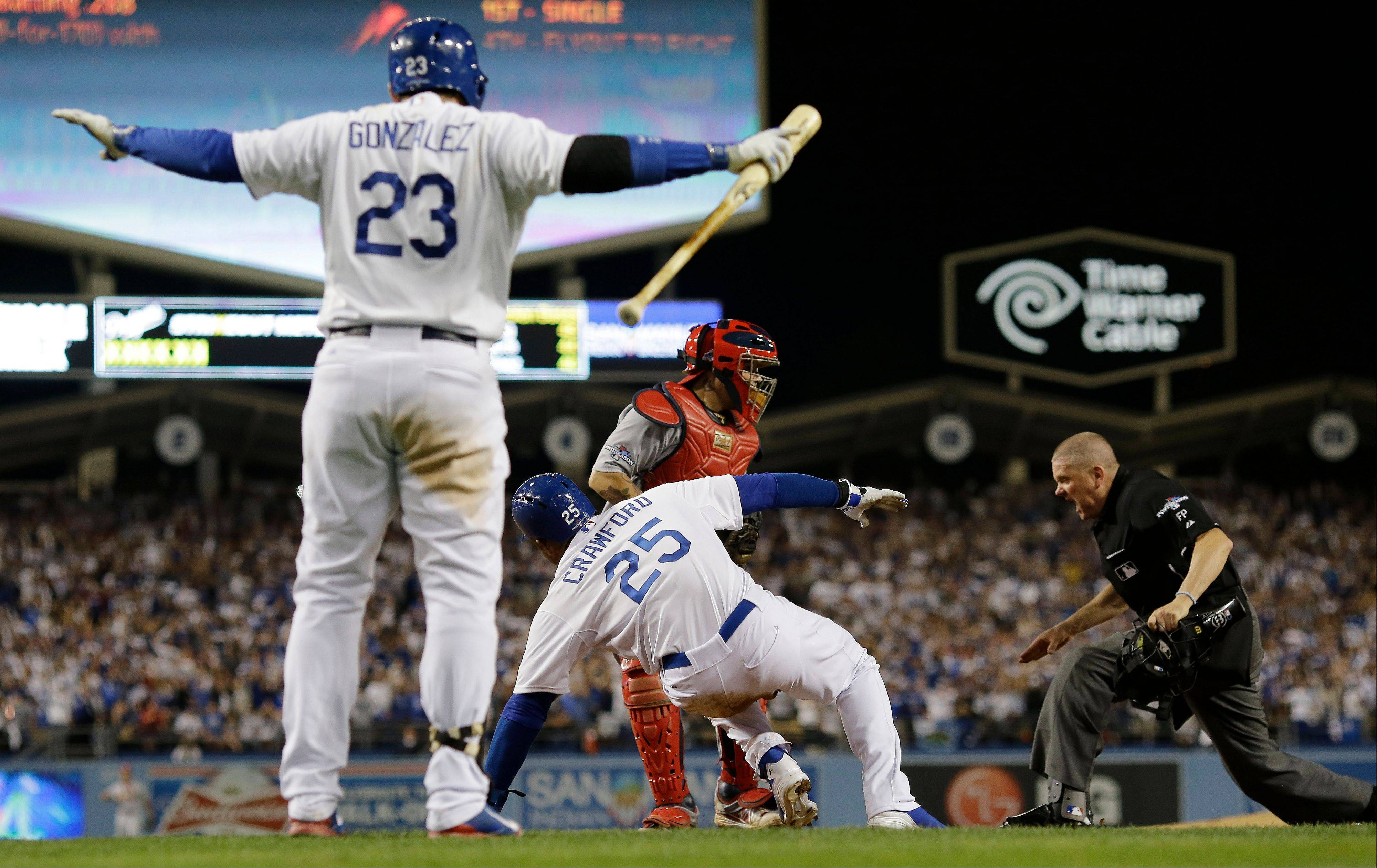 Los Angeles Dodgers' Adrian Gonzalez (23) reacts as Carl Crawford slides safely past St. Louis Cardinals catcher Yadier Molina during the eighth inning of Game 3 of the National League baseball championship series Monday in Los Angeles.