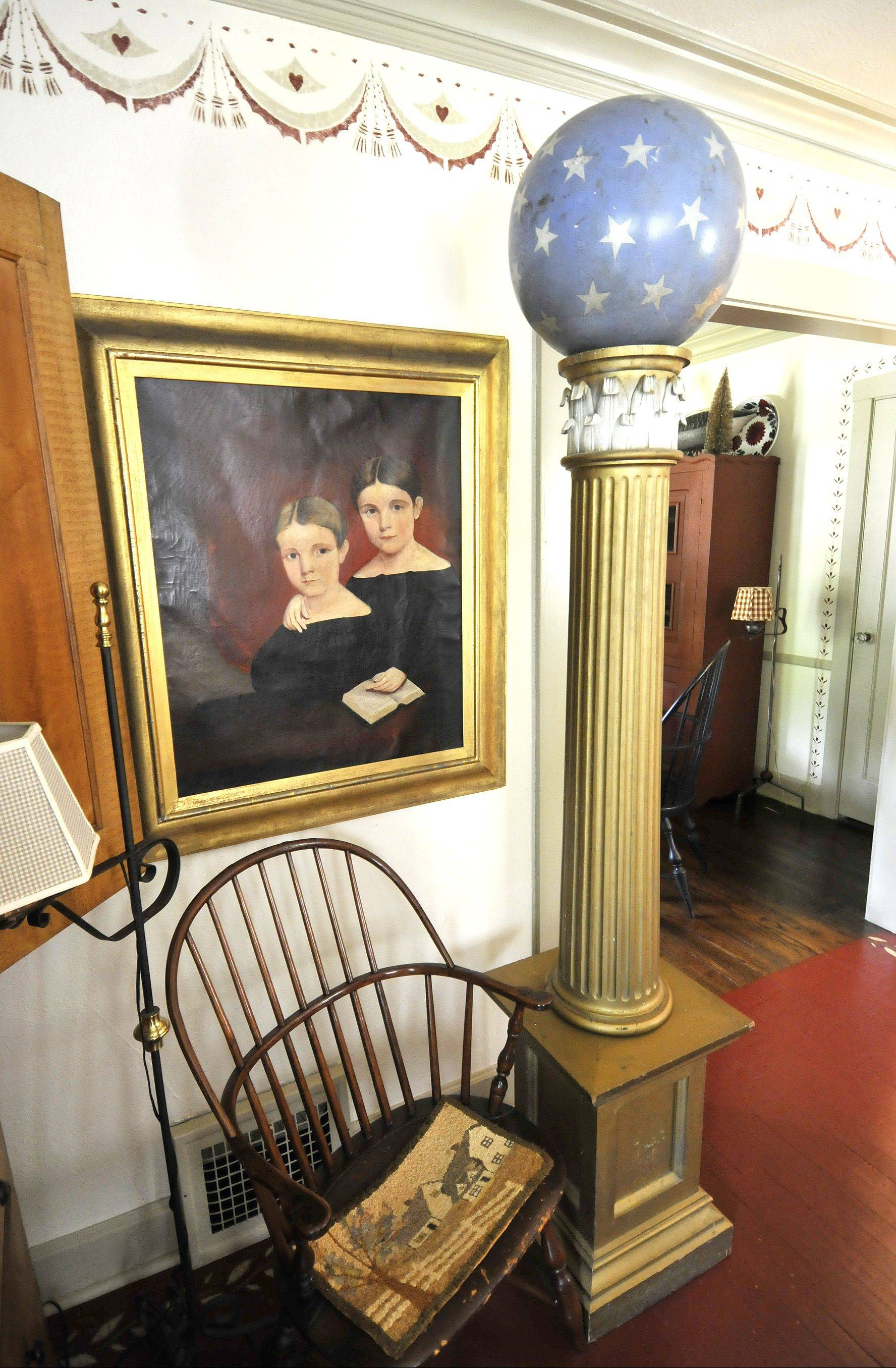 The Larsen's living room is full of antiques, including this double portrait from 1837 featuring a gold leaf ogee curve frame. Also in the photo are a masonic column from 1870 with a ball representing heaven on top, and an American Windsor chair from 1780.