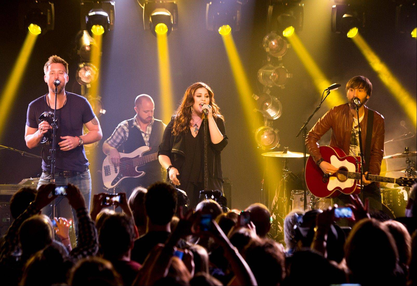 This May 8, 2013 file photo released by iHeartRadio shows members of the band Lady Antebellum, from left, Charles Kelley, Hillary Scott, and Dave Haywood during a performance in New York. Lady Antebellum is postponing the start of its 60-date concert tour. The Nashville, Tenn.-based country music trio says it will now begin the 60-plus city tour Jan. 10 in Peoria. Lady A had been scheduled to start the tour Nov. 8 in Omaha, Neb., and 17 shows will be rescheduled.
