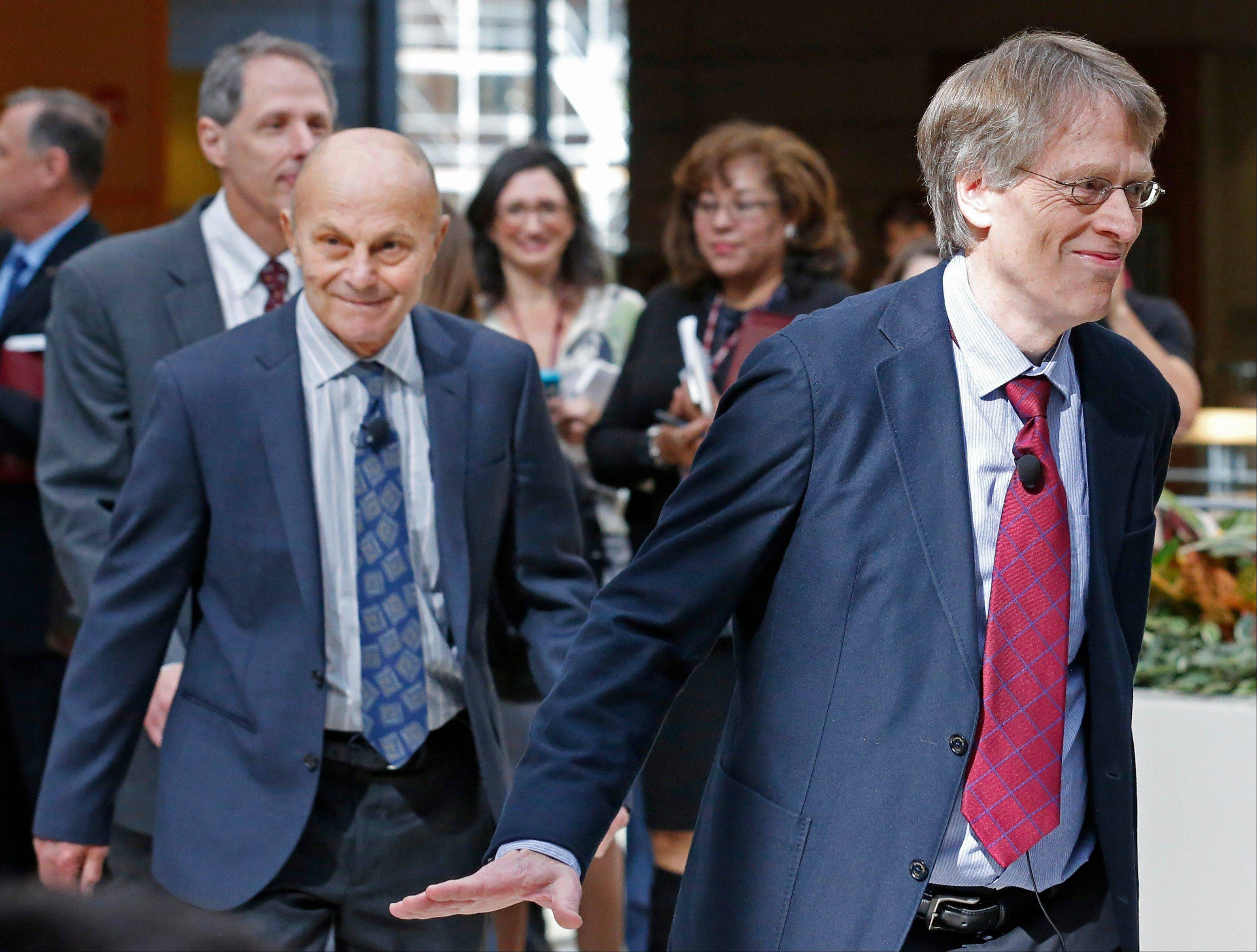 Lars Peter Hansen, 60, right, and Eugene Fama, 74, left, of the University of Chicago arrive at a news conference Monday in Chicago after being named two of the three winners of the Nobel Prize for Economics.