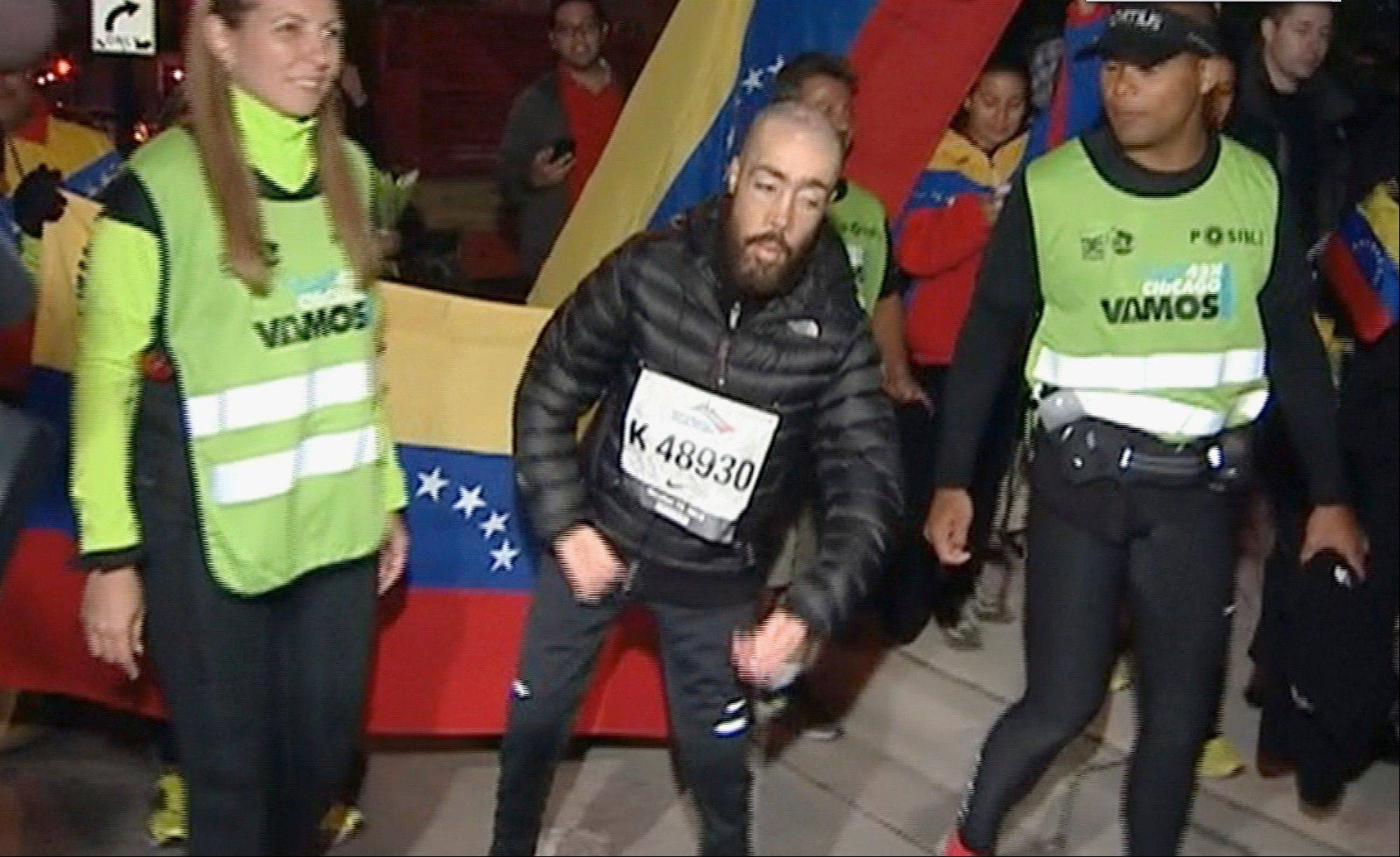 This photo from video shows Maickel Melamed, 38, center, of Venezuela, who has muscular dystrophy, nearing the finish line early Monday as the last runner in the Chicago Marathon.