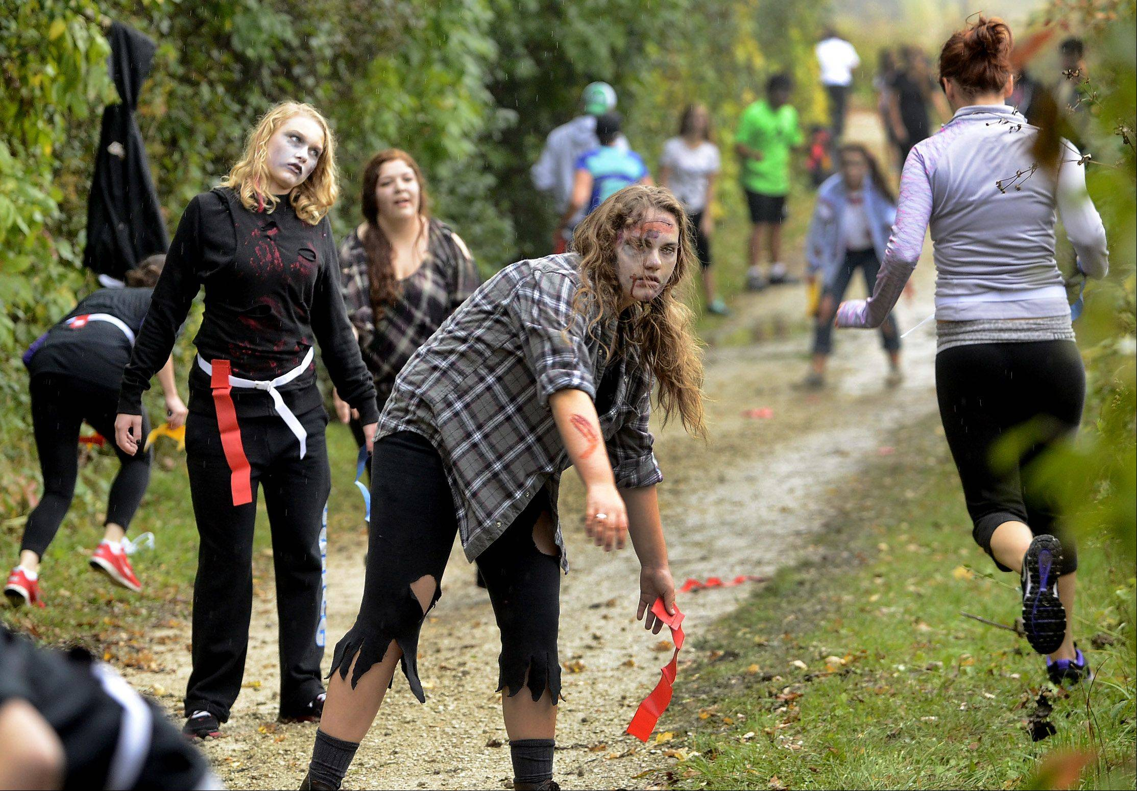 Grayslake North Junior Parker Lawson, center, and fellow Zombies torment runners along the route during Grayslake's Inaugural Zombie Run on Saturday.