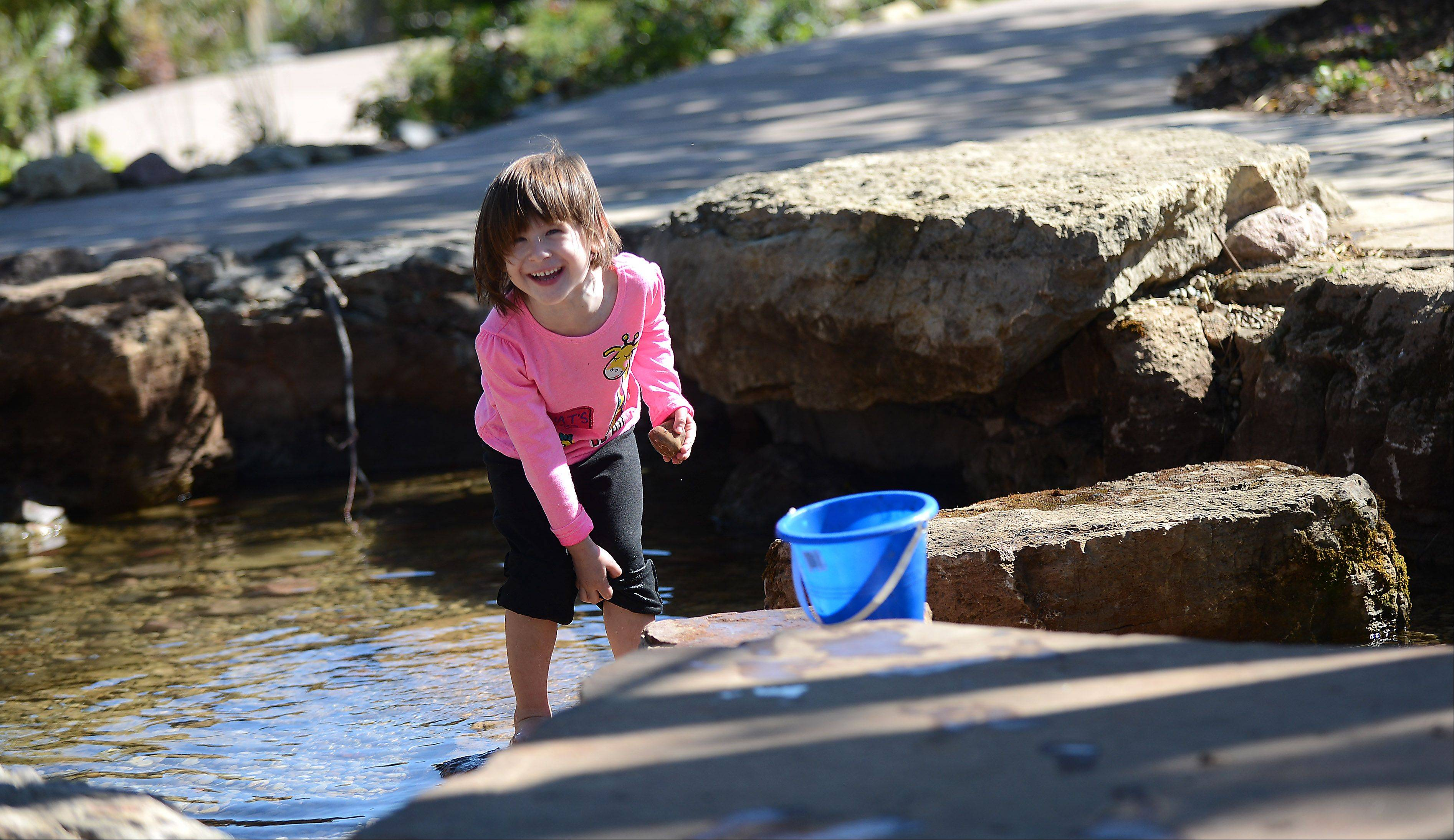 "Kaylie Kojima, 4, of Sugar Grove, smiles at her mom Dena and hikes up her pants after getting wet in ""Kingfisher Crossing"" at Hawks Hollow Nature Playground at Peck Farm Park in Geneva Tuesday. The new play area had it's grand opening last weekend and features natural elements including sand, water, wood and plants. It is designed to engage children in environmental learning."