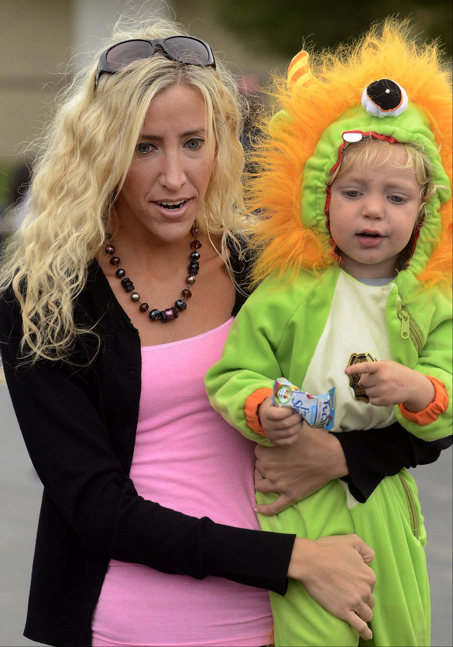 Dressed as a monster, Marley Fox is held by his mom Jordana Fox, while waiting to board a truck during Trucks, Trunks and Treats at the Vernon Hills Sullivan Community Center Saturday.