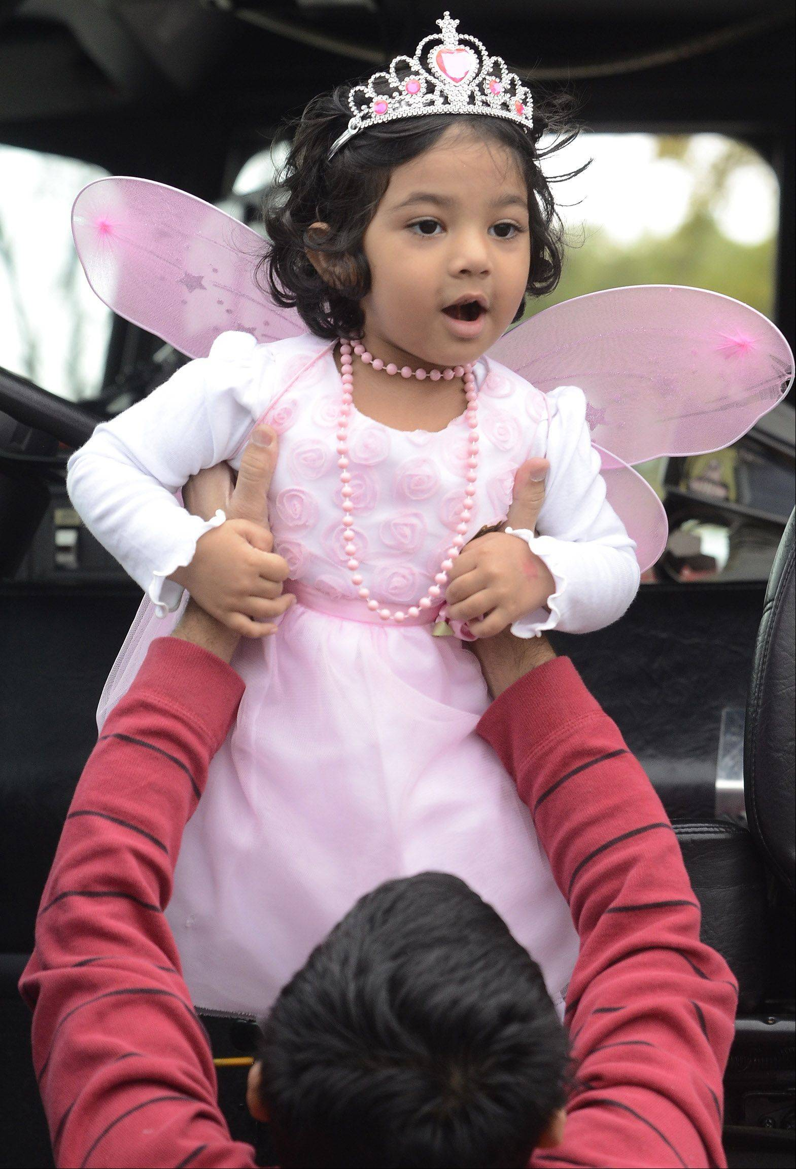 Dressed as a princess, Stuti Jain is helped down from a fire truck by her dad Ashish, during Trucks, Trunks and Treats at the Vernon Hills Sullivan Community Center Saturday.