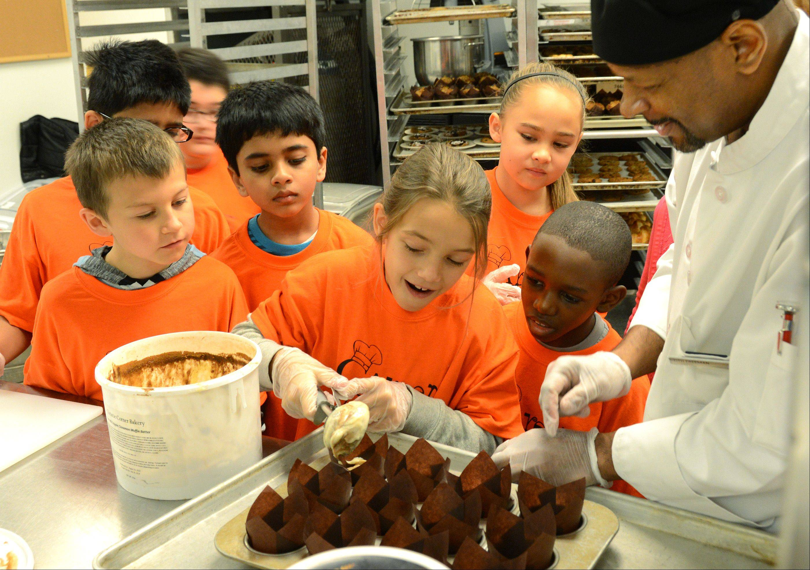 Surrounded by her classmates, Amelia Gesicki tries her hand at making apple cinnamon muffins under the watchful eye of Executive Chef Keith Freeman, right. Fourth graders from Stella May Swartz school in Oakbrook Terrace got an inside look Monday at the operation of the Hilton Suites hotel in Oakbrook Terrace.
