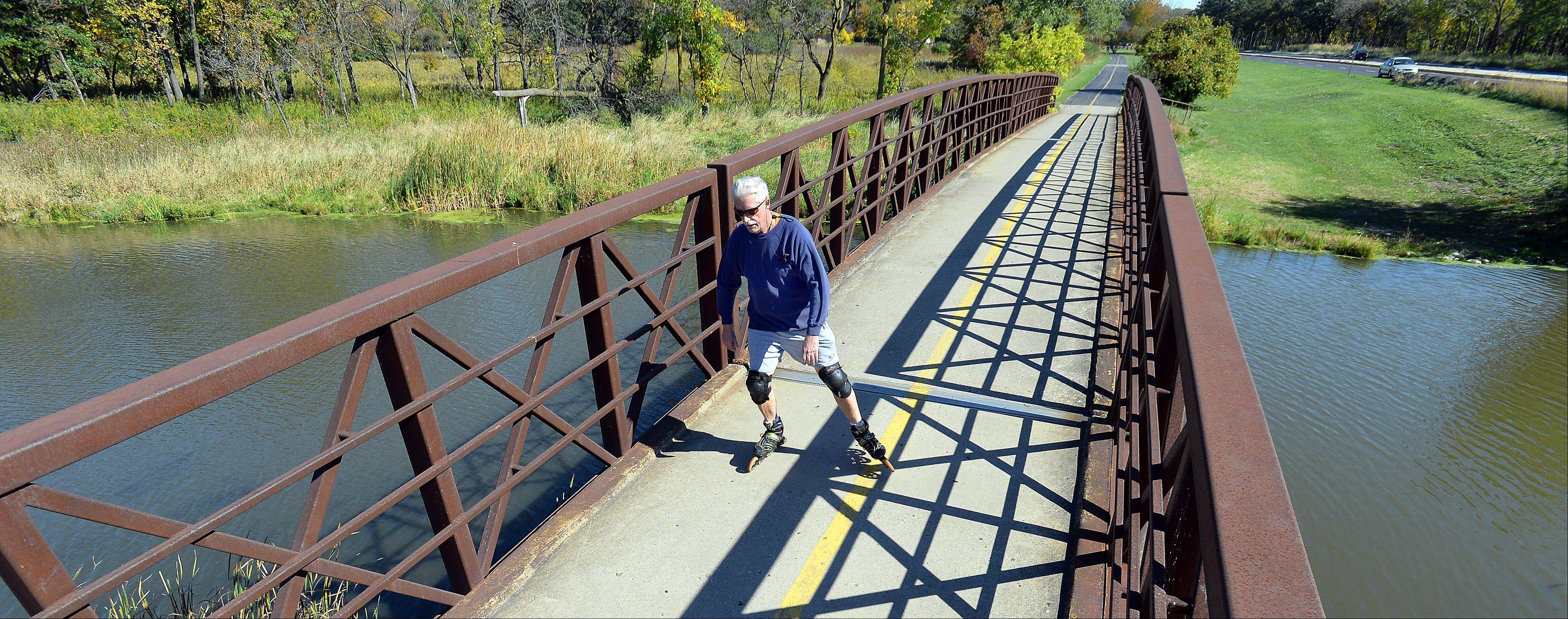Neil Stout, 64, of Schaumburg, crosses the bridge next to Higgins Road on Monday afternoon as he does five times a weeks in a ten-mile loop on the Busse Forest West bicycle trail for exercise and good clean air.