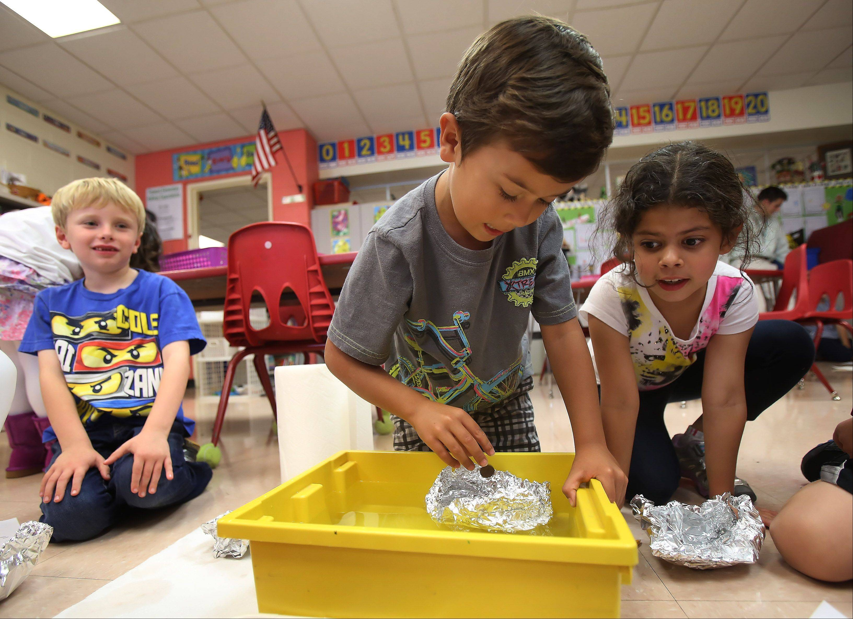 First graders Kristian Garcia, center, and Lucia Buckley, from Laura McCathy's class, place pennies in a boat as they conduct experiments Tuesday at Fremont Elementary School in Mundelein. As part of a Columbus Day project, students designed boats to hold as many pennies as they could until they sank.