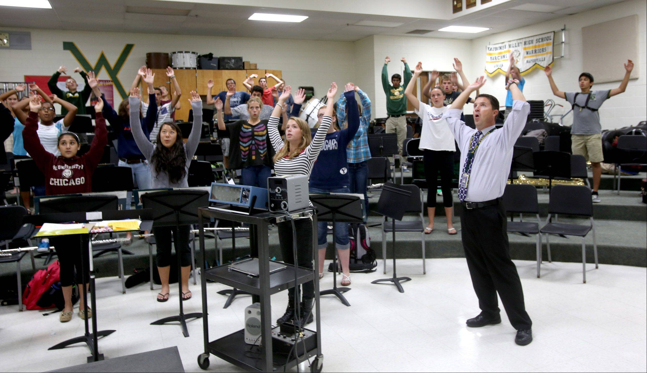 Mark Duker, chairman of the fine arts department at Waubonsie Valley High School in Aurora, leads the Wind Ensemble in stretching and breathing exercises before rehearsal. Duker is one of 25 semifinalists for the first Grammy Award for music educators.