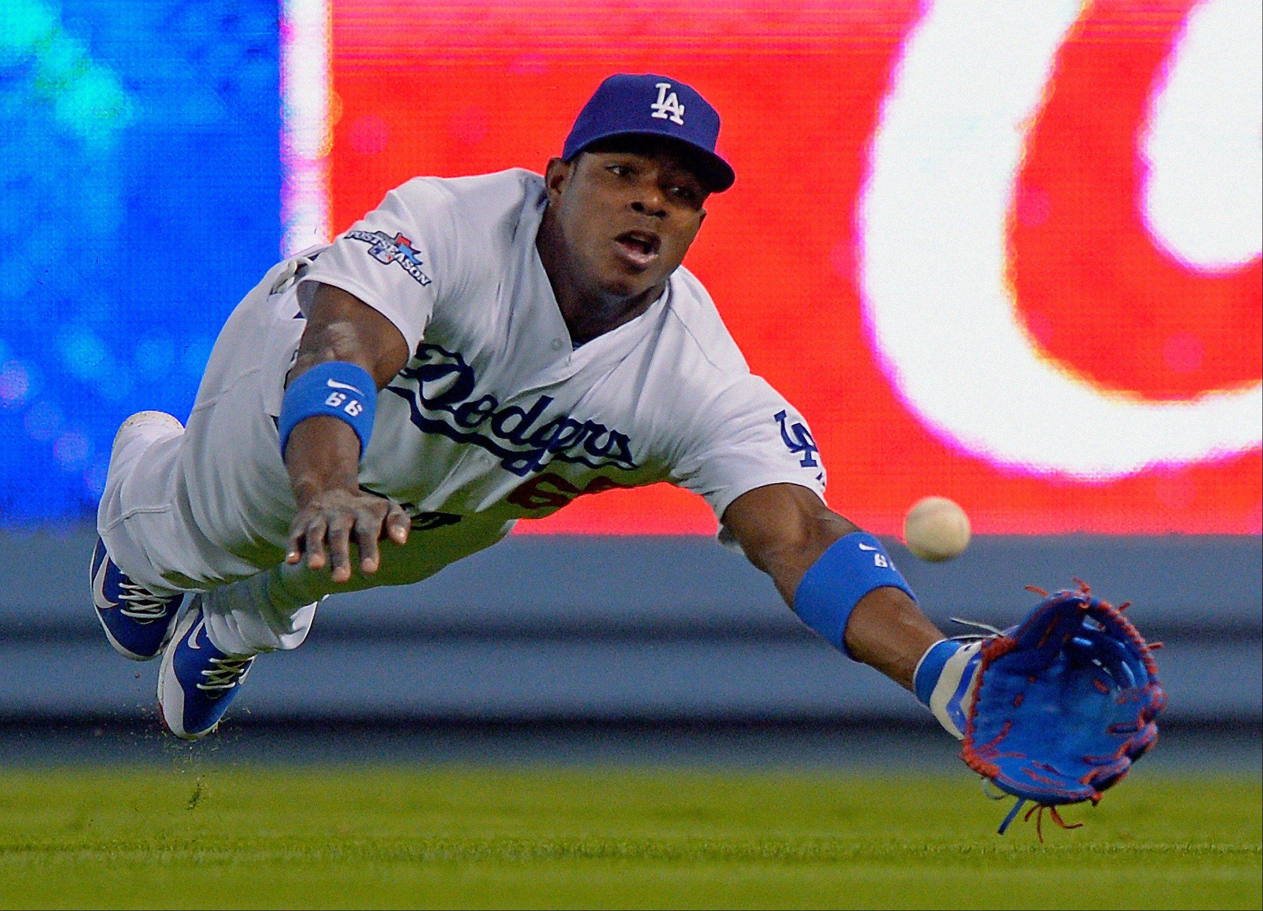 The Dodgers' Yasiel Puig dives for a ball hit by the Cardinals' David Freese during the fifth inning of Game 3 of the National League Championship Series on Monday in Los Angeles. The ball eluded Puig for a hit.