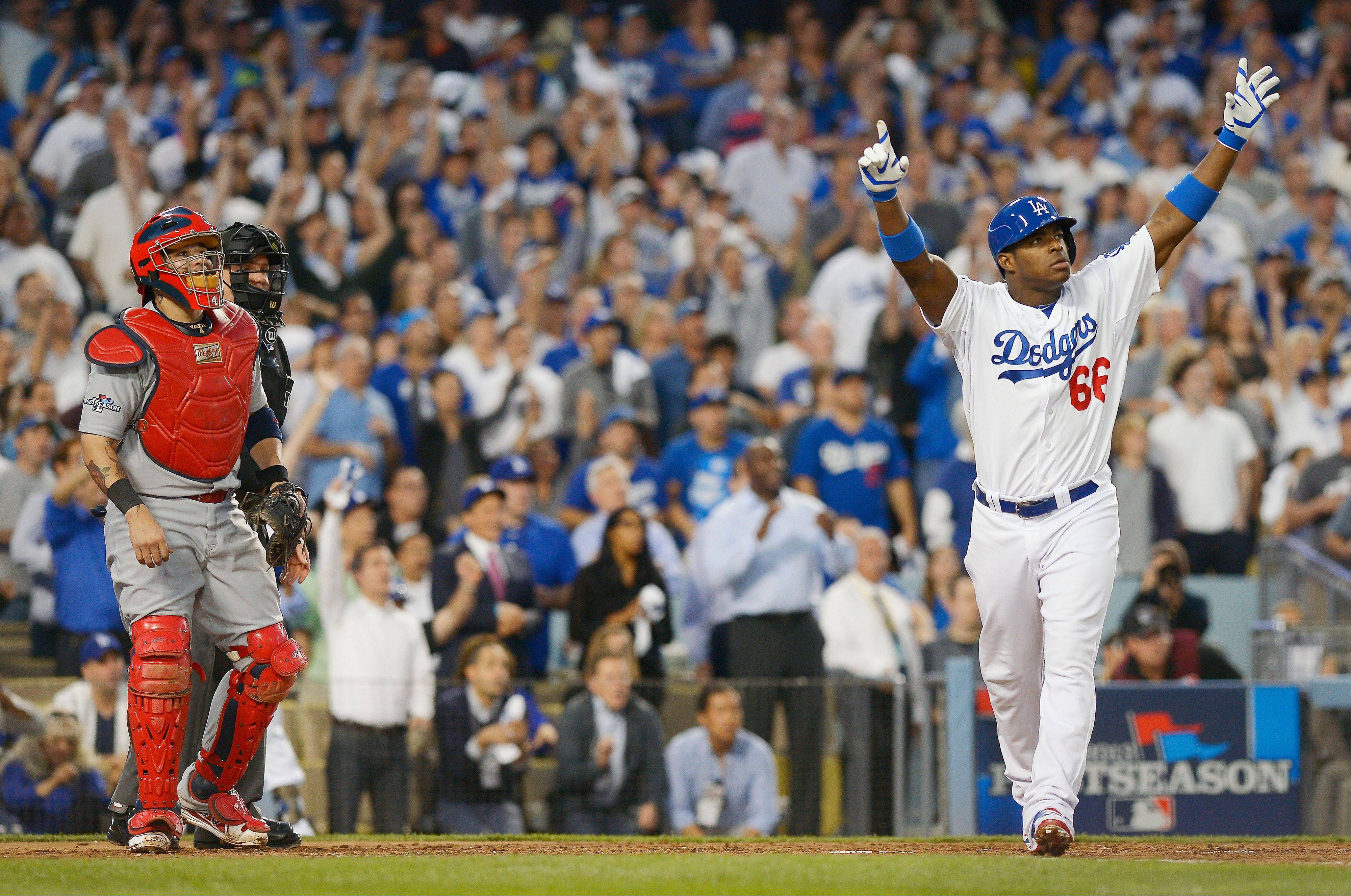 The Dodgers' Yasiel Puig celebrates at the plate after hitting an RBI triple during the fourth inning.