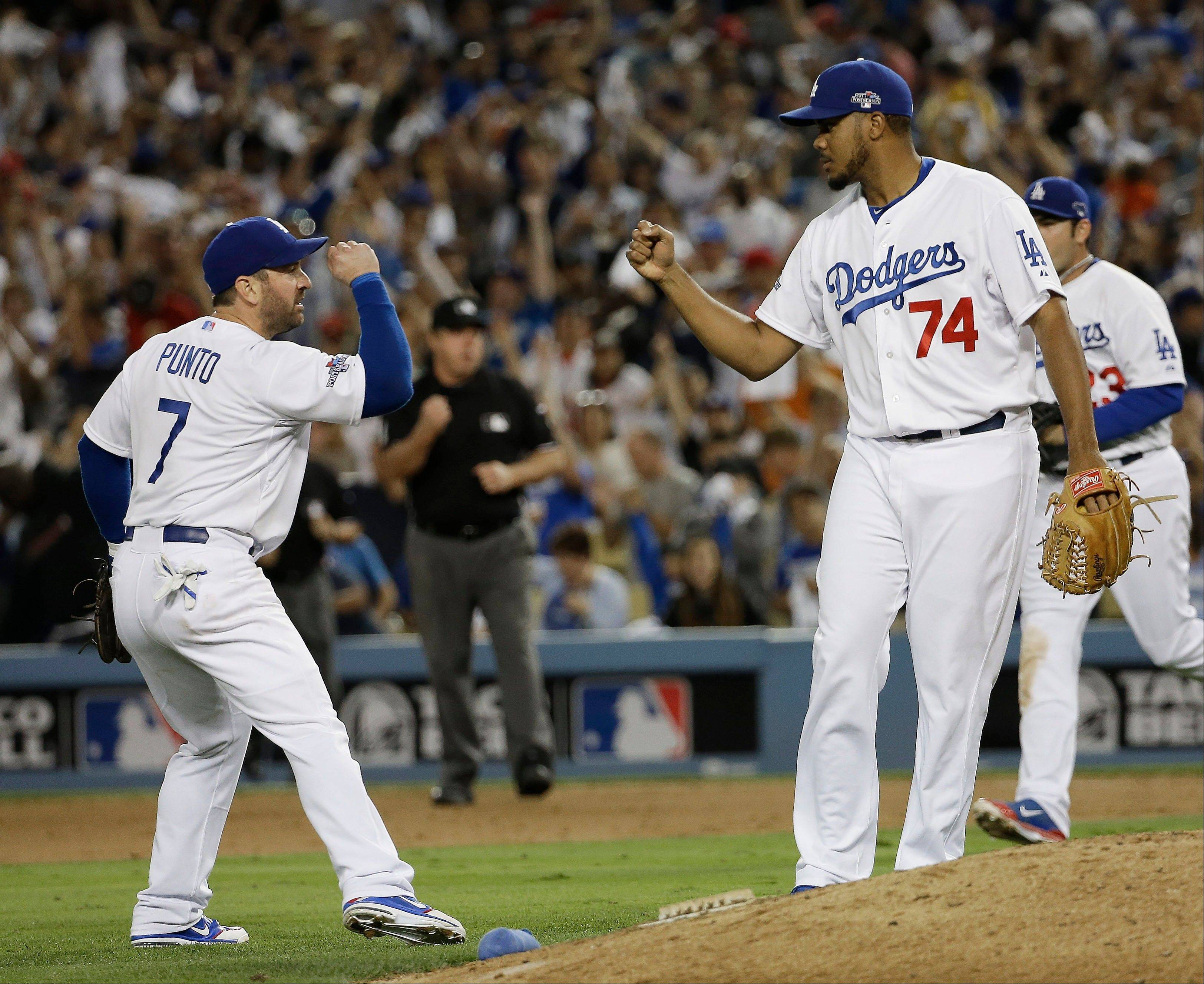 The Dodgers' Nick Punto (7) and Kenley Jansen celebrate after Game 3.