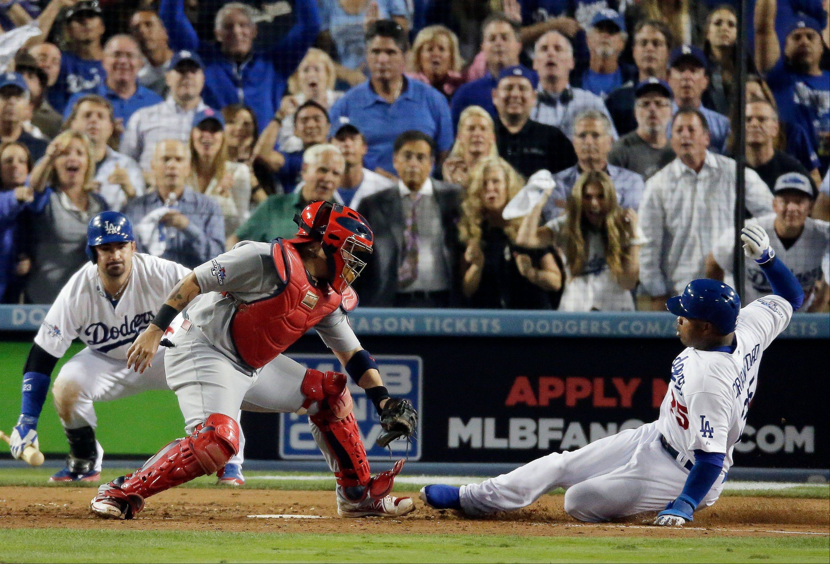The Dodgers' Carl Crawford slides safely past St. Louis Cardinals catcher Yadier Molina during the eighth inning Monday in Game 3.