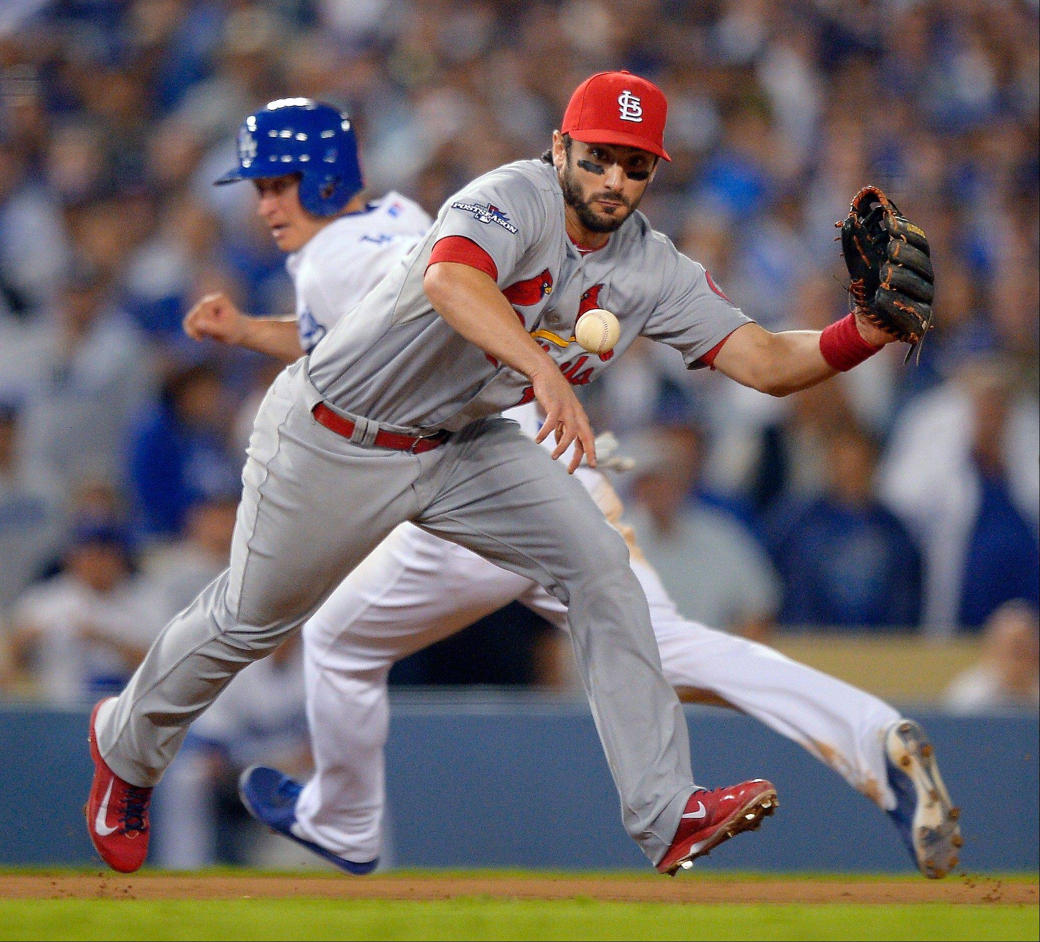 The Cardinals' Matt Carpenter fields a ground ball hit by the Dodgers' Adrian Gonzalez as Mark Ellis advances to third during the eighth inning.
