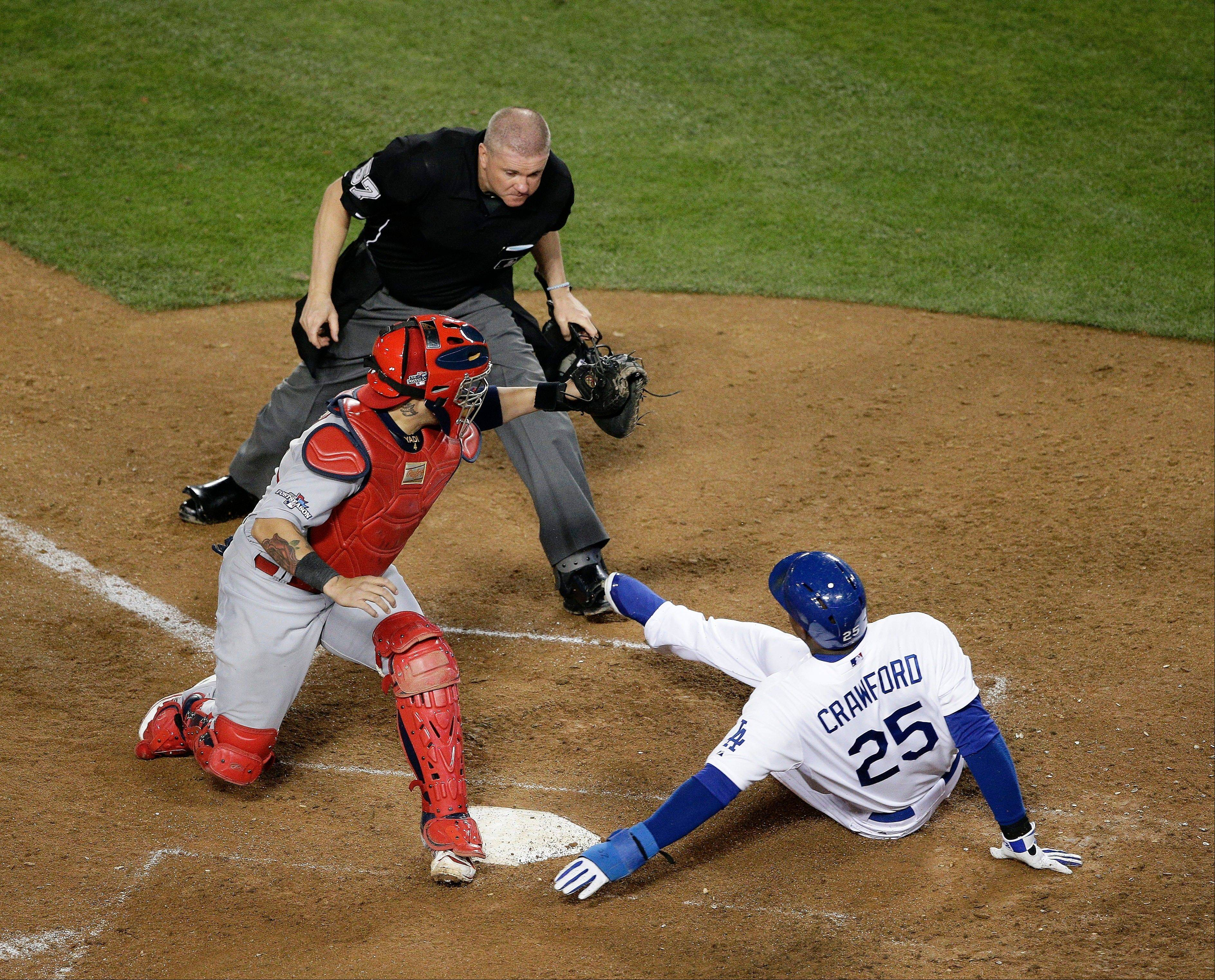 The Dodgers' Carl Crawford slides safely past St. Louis Cardinals catcher Yadier Molina.