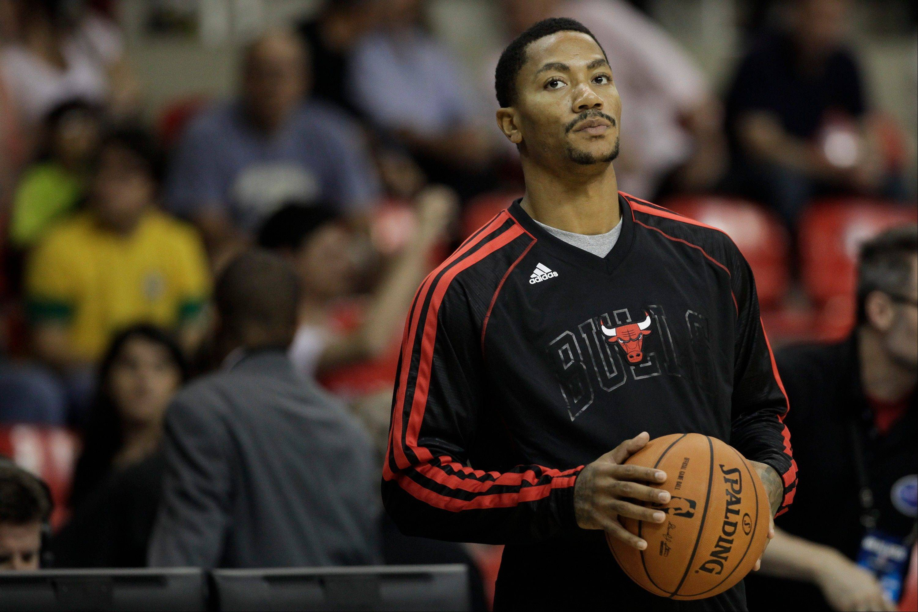 Derrick Rose watches as his Bulls teammates warm up before their preseason game against the Washington Wizards in Brazil on Saturday. Rose missed sat out the game with soreness in his surgically repaired left knee.