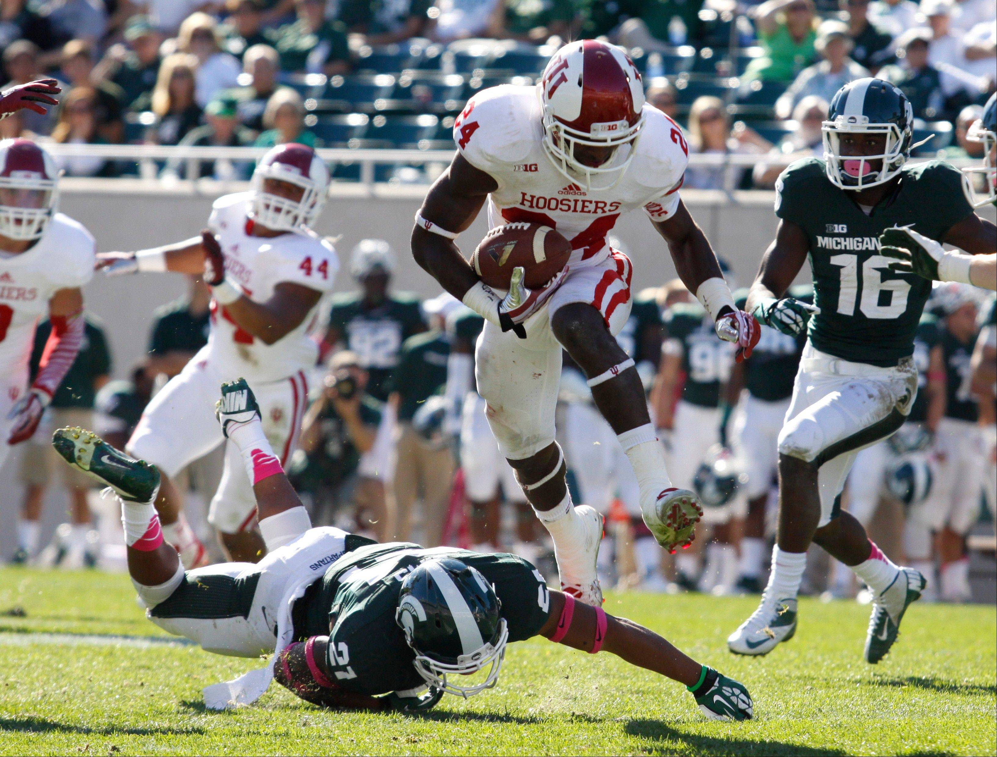 Indiana cornerback Tim Bennett hurdles Michigan State receiver Andre Sims Jr. while returning an interception during the fourth quarter of Saturday's game in East Lansing, Mich. Michigan State won 42-28.
