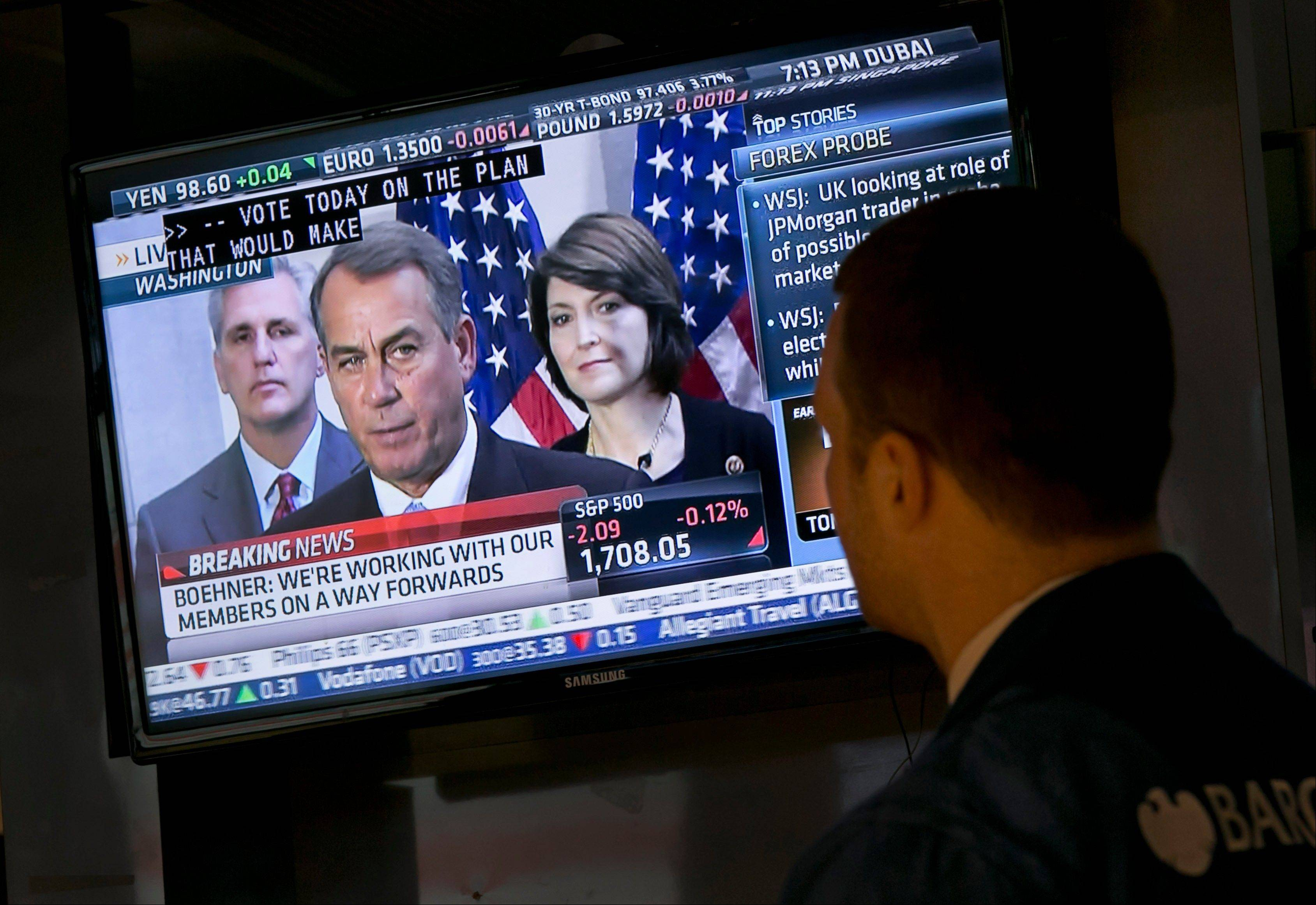 A trader watches a television monitor on the floor of the New York Stock Exchange showing a Washington news conference by House Speaker John Boehner on Tuesday.