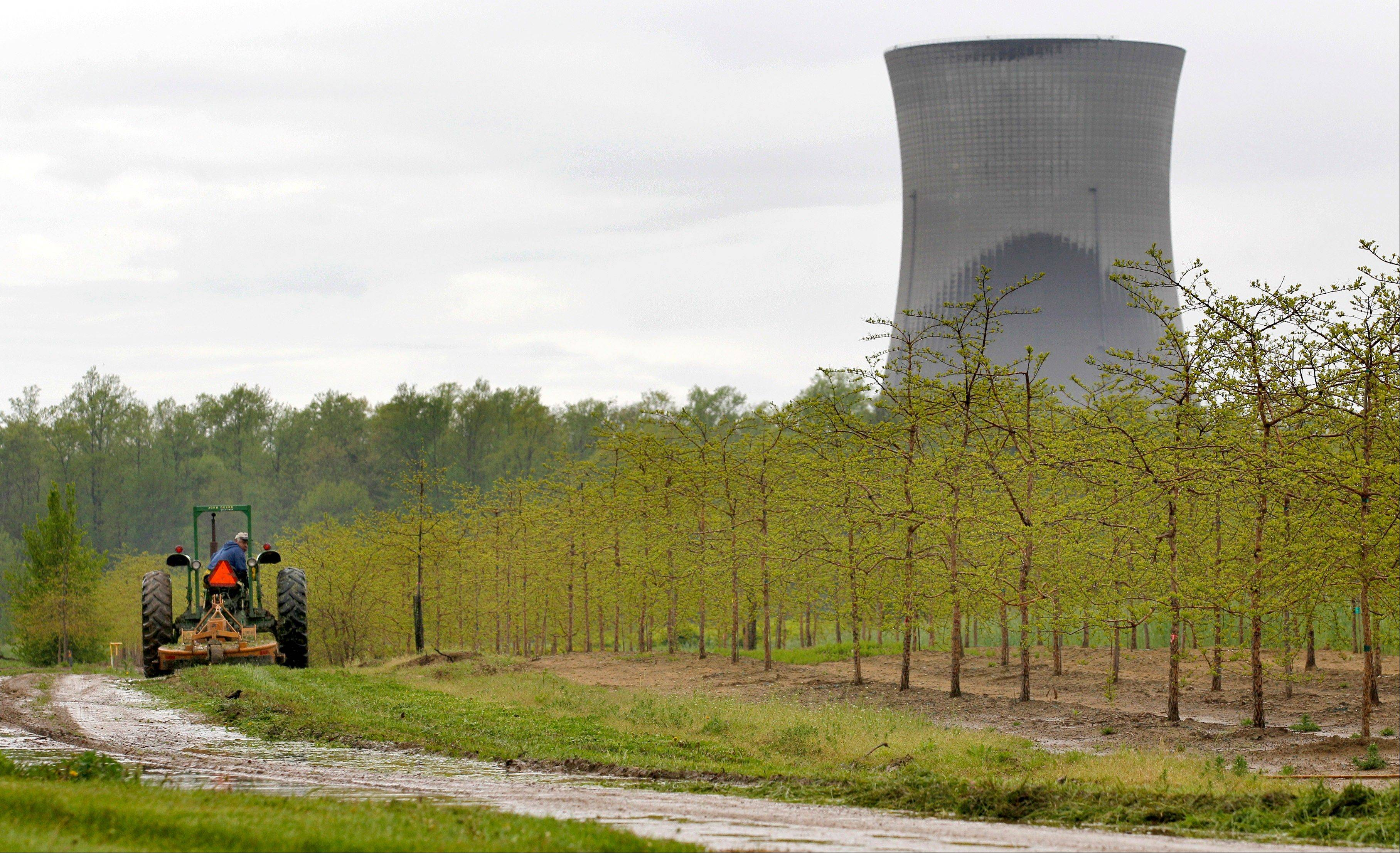 A worker drives a tractor at a tree farm in North Perry, Ohio, near the cooling towers of the Perry Nuclear Power Plant. A study determined that six Illinois nuclear power plants logged hundreds of safety violations from 2000 through 2012, most of them considered low-level.