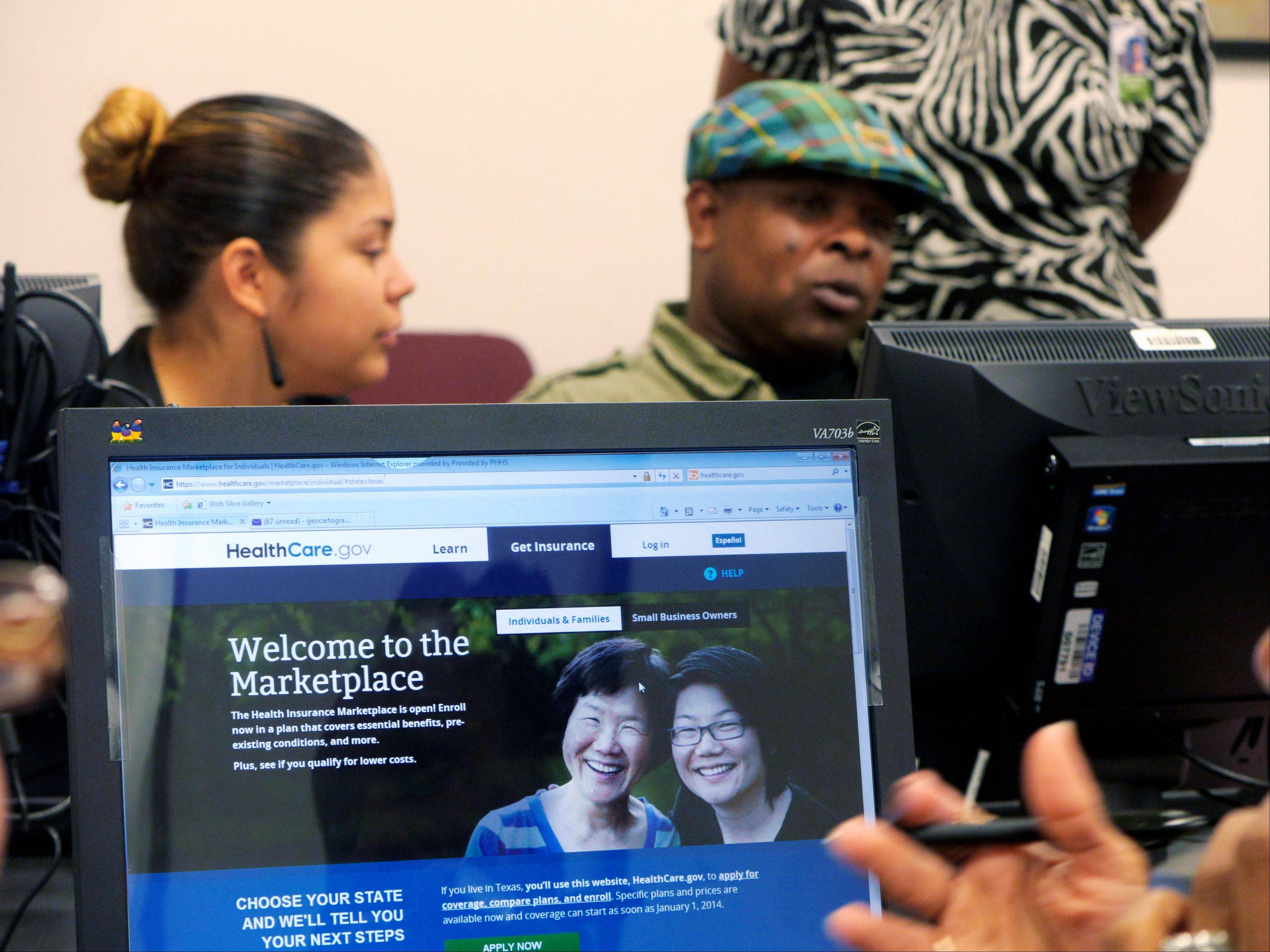 Parkland Memorial Hospital financial counselor Tiffany Ruiz, left, helps Vyncent Bosh sign up for insurance under the Affordable Care Act last week in Dallas.