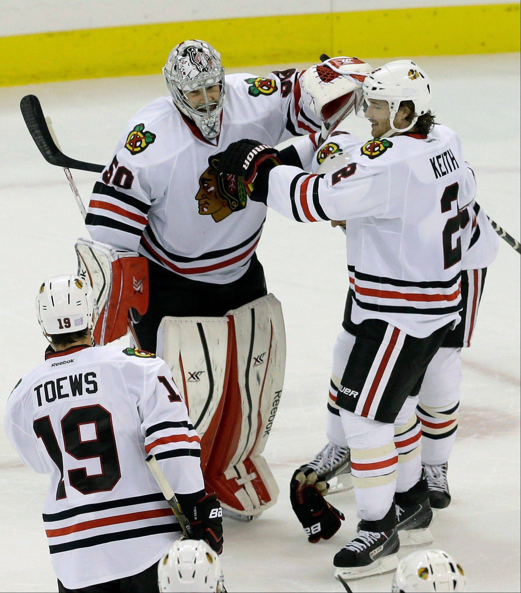 Chicago Blackhawks goalie Corey Crawford (50) is congratulated by Duncan Keith (2) and Jonathan Toews (19) following a shootout during an NHL hockey game against the Carolina Hurricanes in Raleigh, N.C., Tuesday, Oct. 15, 2013. Chicago won 3-2. (AP Photo/Gerry Broome)