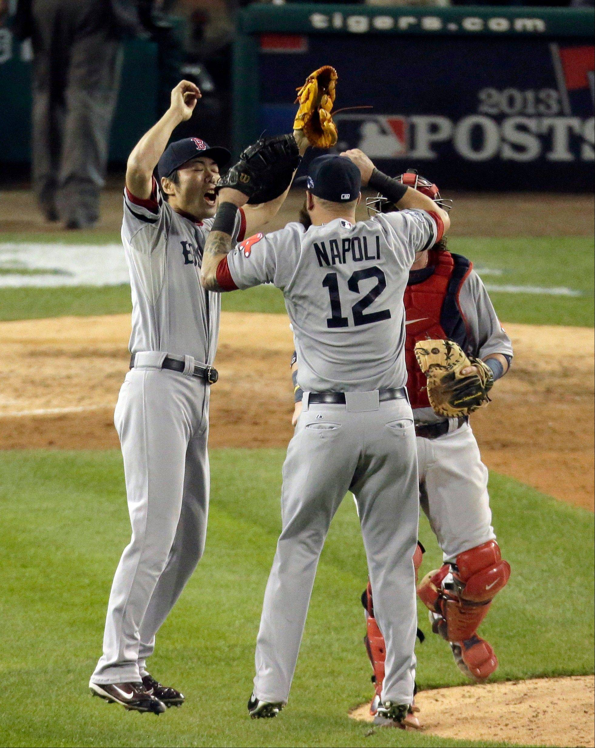 Relief pitcher Koji Uehara, left, celebrates with Mike Napoli and Jarrod Saltalamacchia after the Red Sox defeated the Detroit Tigers 1-0 in Game 3 of the American League Championship Series on Tuesday in Detroit.