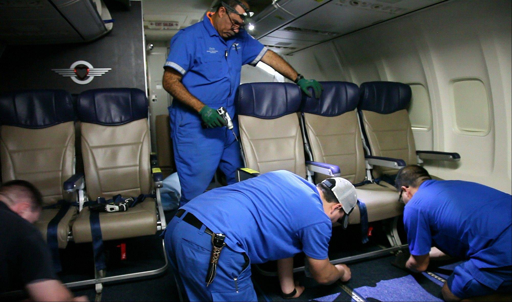 Southwest Airlines aircraft technicians install newer, skinnier seats on a 737 at the carrier's headquarters in Dallas.