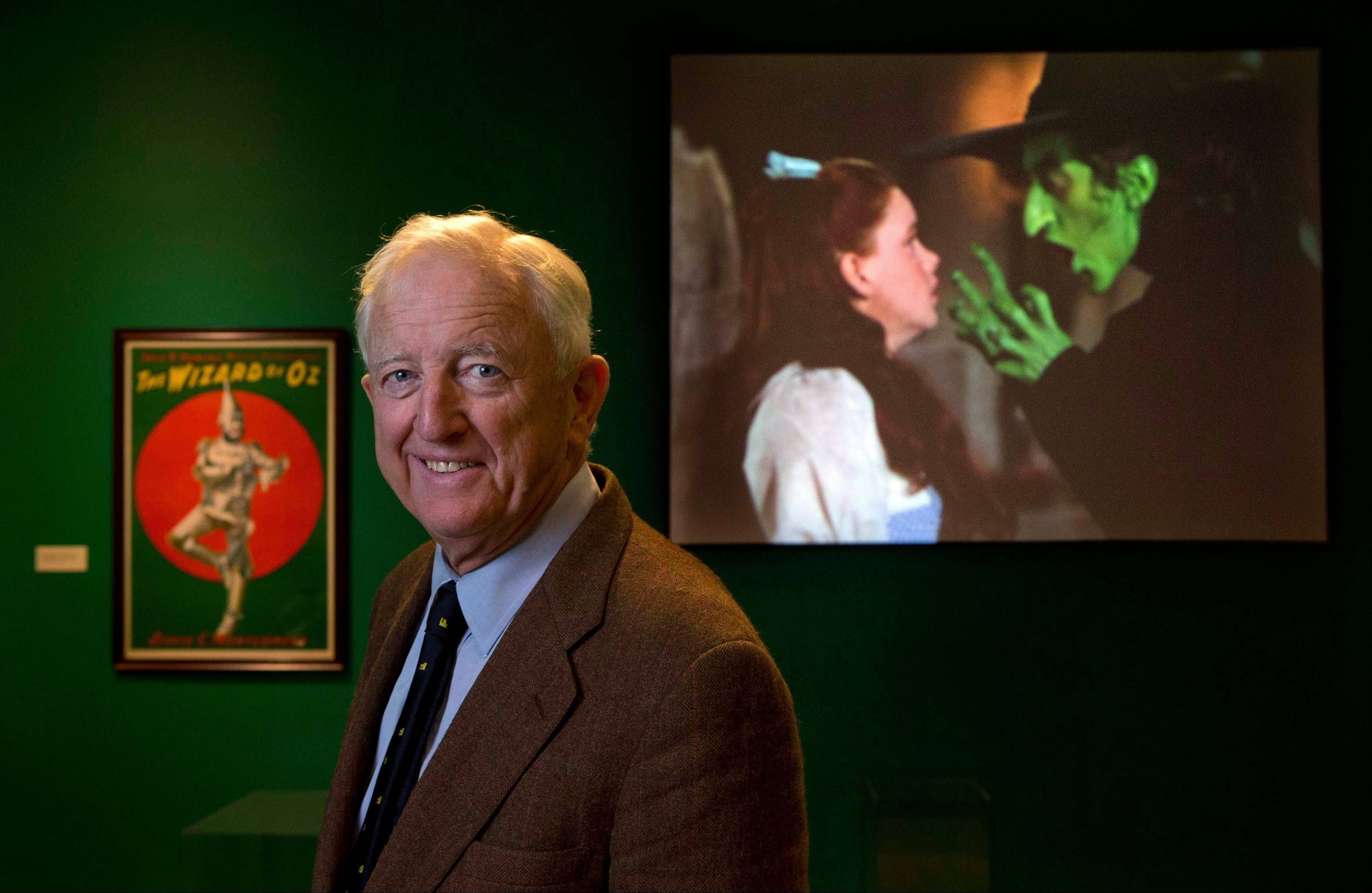 "Ham Meserve, of Southport, Maine, the son of actress Margaret Hamilton, poses at the Farnsworth Museum, in Rockland, Maine. Hamilton is seen on the screen at right playing the role of the wicked witch of the West in the movie, ""The Wizard of Oz."""