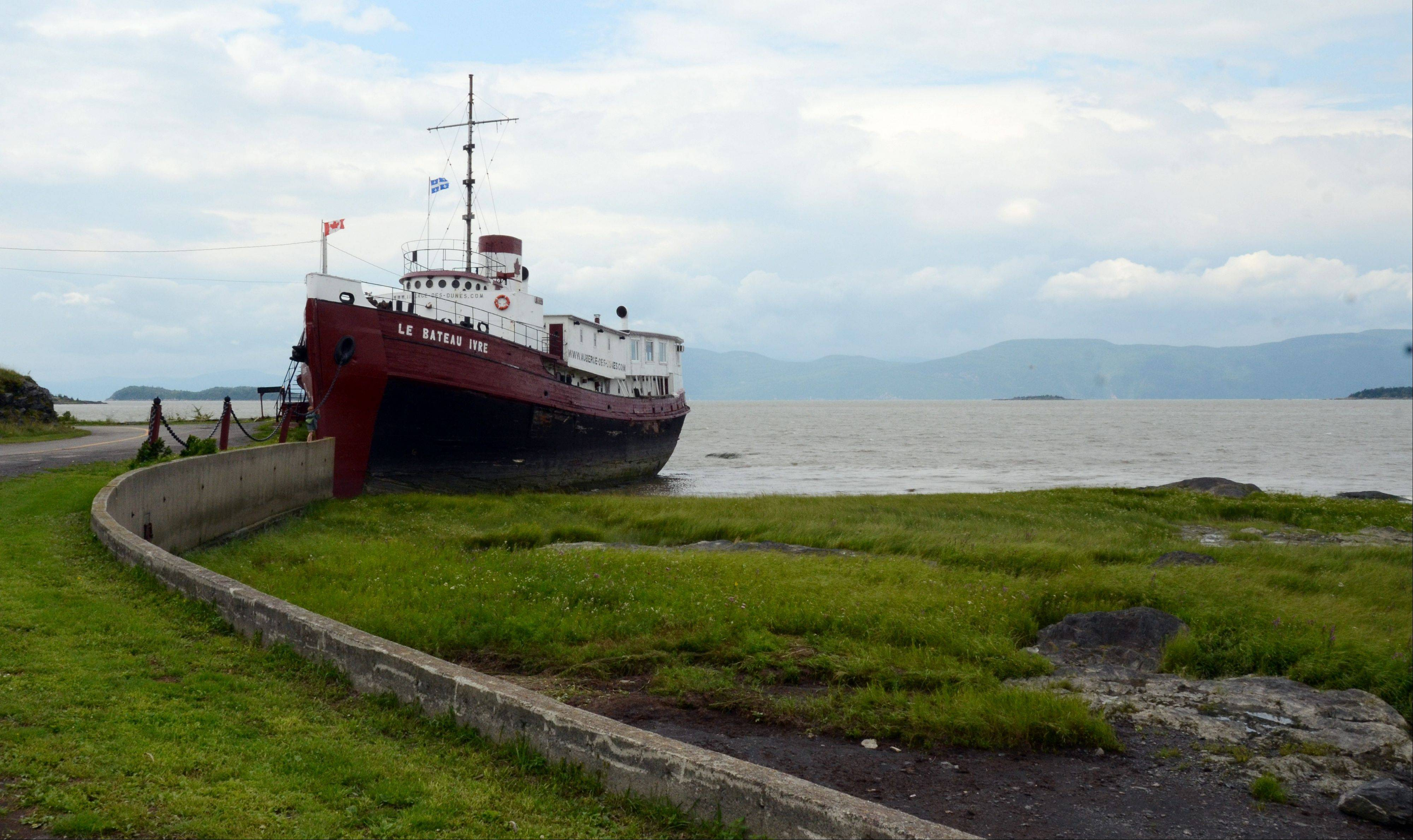 An old New York tugboat converted to a restaurant and social center floats along Ile-aux-Grues in the St. Lawrence River on the outskirts of Quebec City. The island offers quiet roads and stunning river vistas for cyclists and lovers of solitude.