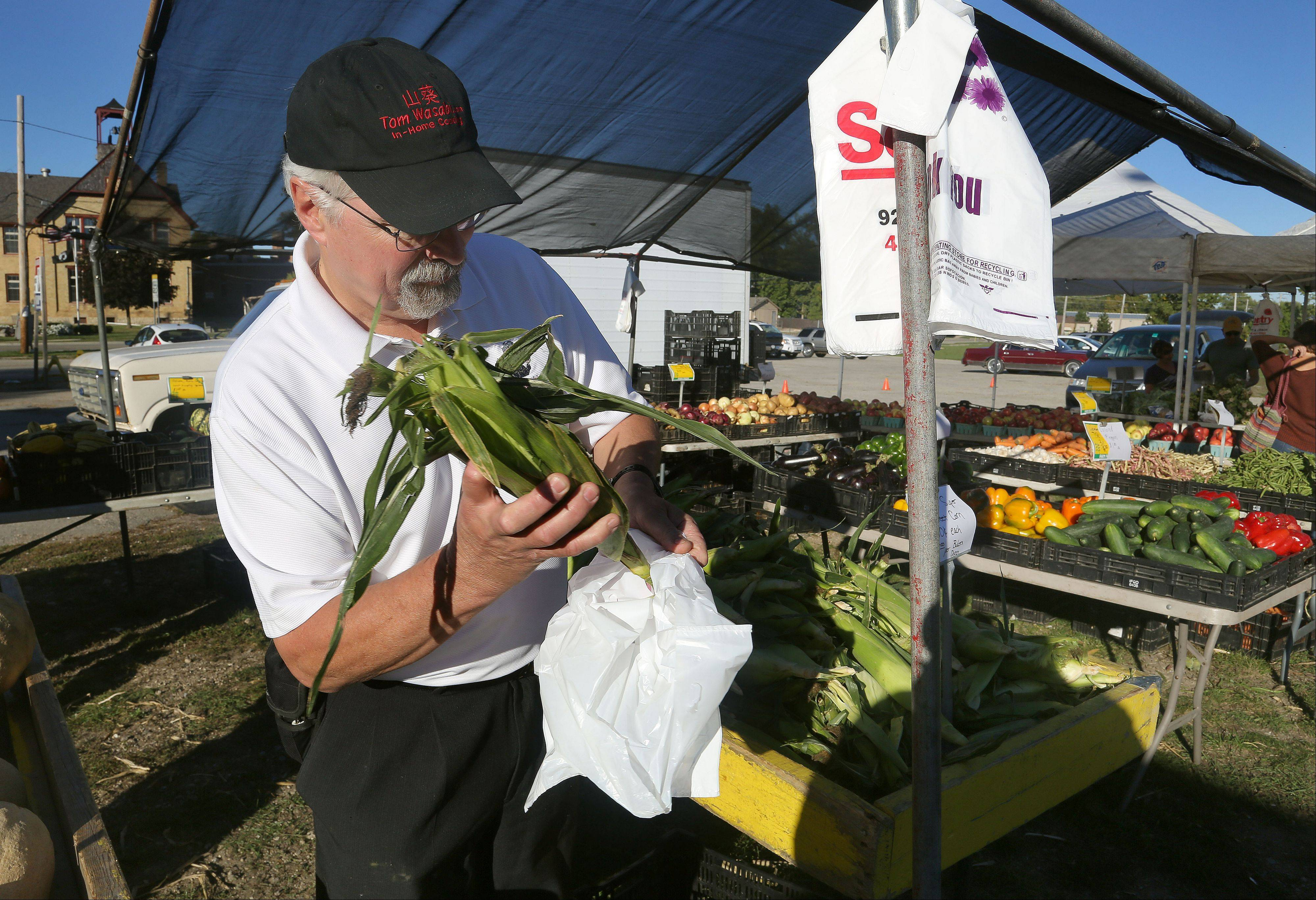 Thomas Craner of Antioch shops for sweet corn at the Antioch farmers market. He teaches students of this Tom Wasabi In-Home Cooking School to opt for fresh ingredients over processed foods.