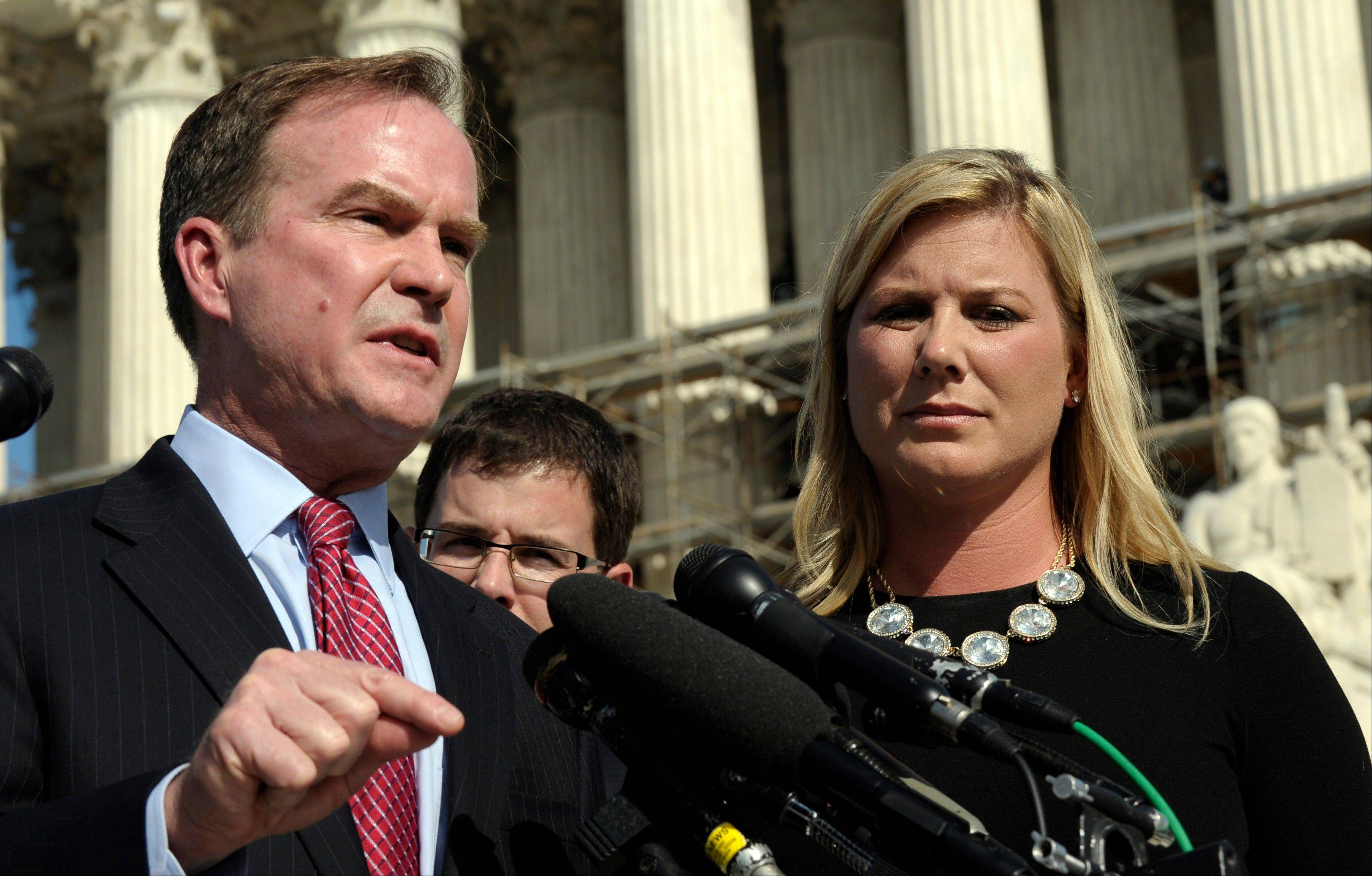 Michigan Attorney General Bill Schuette, left, standing with Jennifer Gratz, chief executive officer of XIV Foundation, speaks to reporters after arguing their case before the Supreme Court Tuesday.