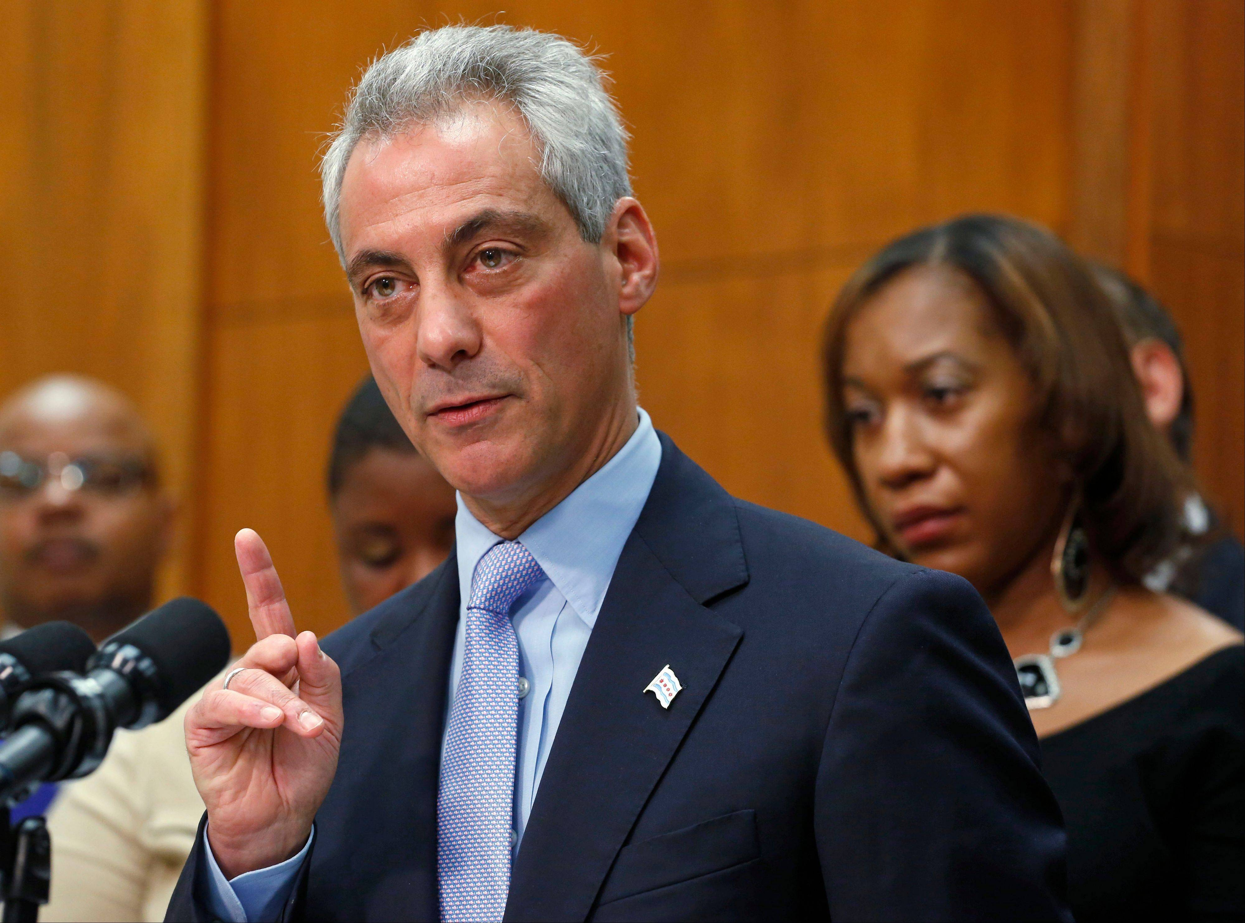 Chicago Mayor Rahm Emanuel speaks at a Tuesday news conference surrounded by the members of families affected by gun violence.