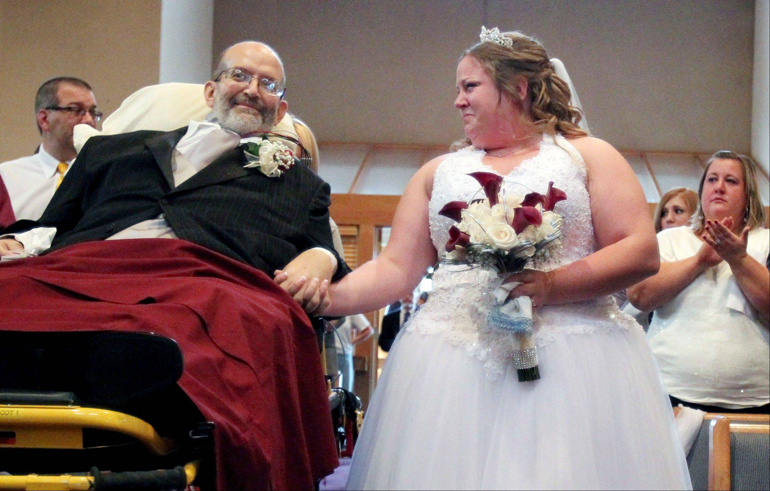 Bride Sarah Nagy, right, begins to cry as she is escorted by her father, Scott, down the aisle during her wedding ceremony Oct. 12, 2013 at First Lutheran Church in Strongsville, Ohio. University Hospital sent a medical team along with Scott, who is bound to his bed, and the ambulance ride to the church was donated by Physicians Medical Transport.