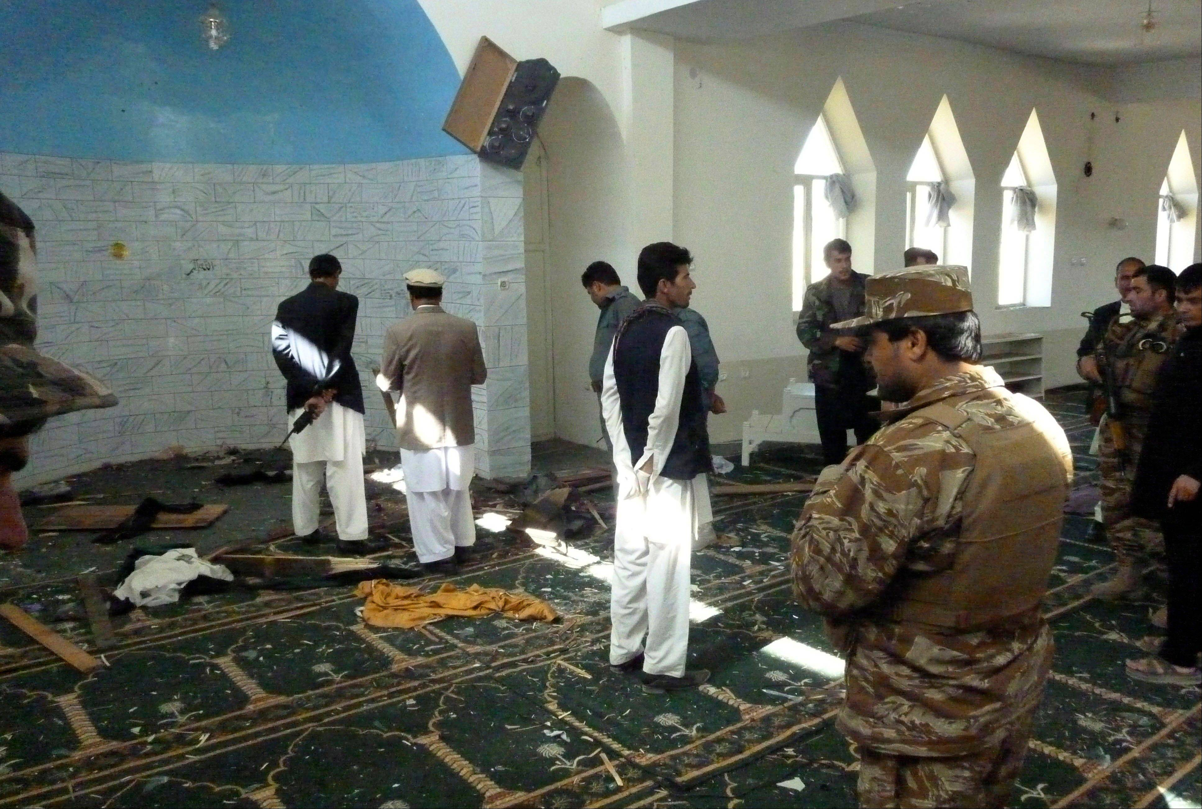Afghan police and officials examine the mosque in Puli Alam, Logar Province, Afghanistan, where a bomb hidden in the base of a microphone killed Afghan Governor Arsallah Jamal, Tuesday, Oct 15, 2013. No one immediately claimed responsibility for the attack but the Taliban have been targeting Afghan officials, military and NATO troops as part of a campaign to retake territory as international troops draw down ahead of a full pullout at the end of 2014.