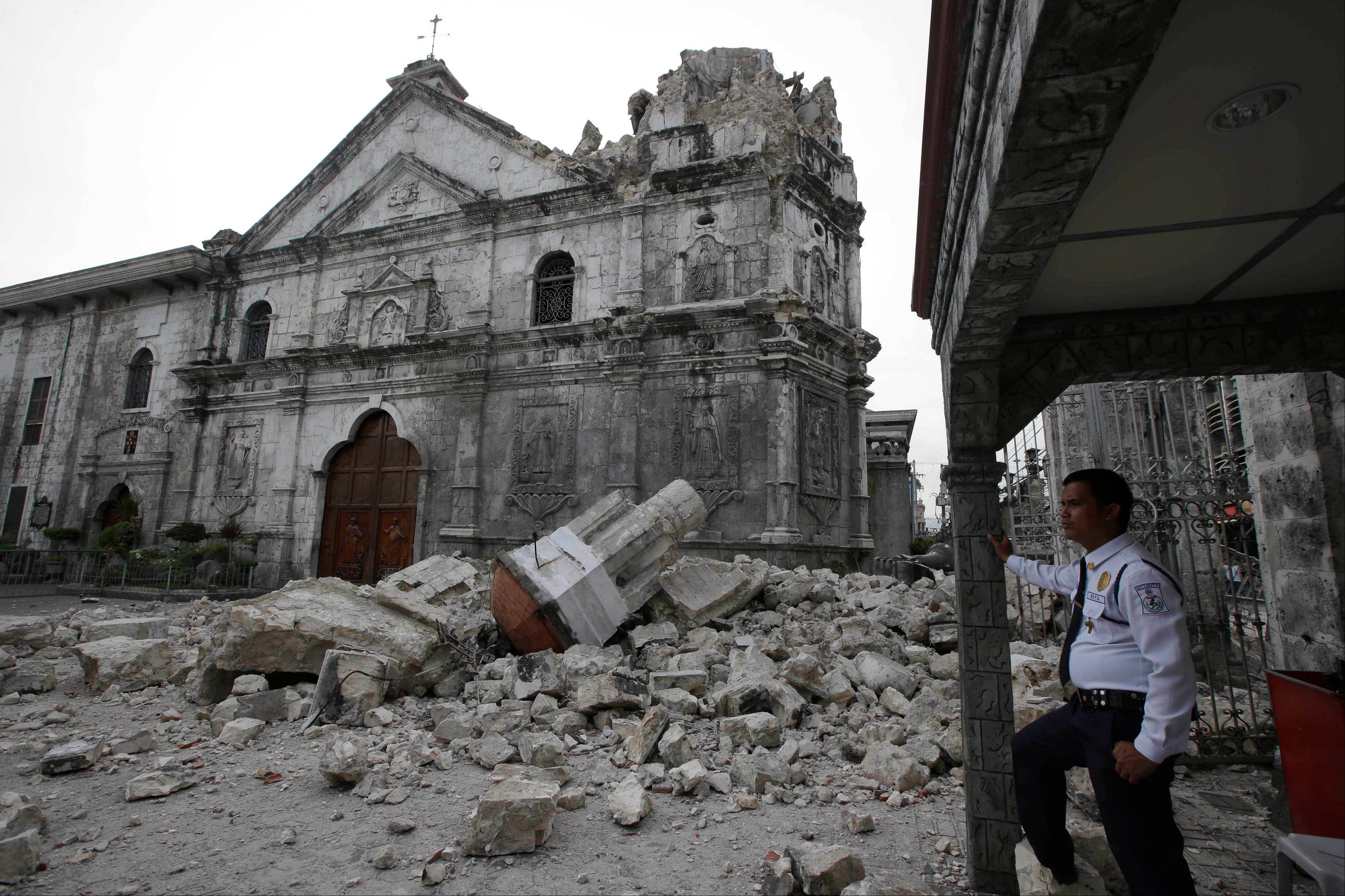 A private guard stands near the damaged Basilica of the Holy Child following a 7.2-magnitude earthquake that hit Cebu city in central Philippines and toppled the bell tower of the Philippines' oldest church Tuesday, Oct. 15, 2013. The tremor collapsed buildings, cracked roads and toppled the bell tower of the church Tuesday morning, causing multiple deaths across the central region and sending terrified residents into deadly stampedes.