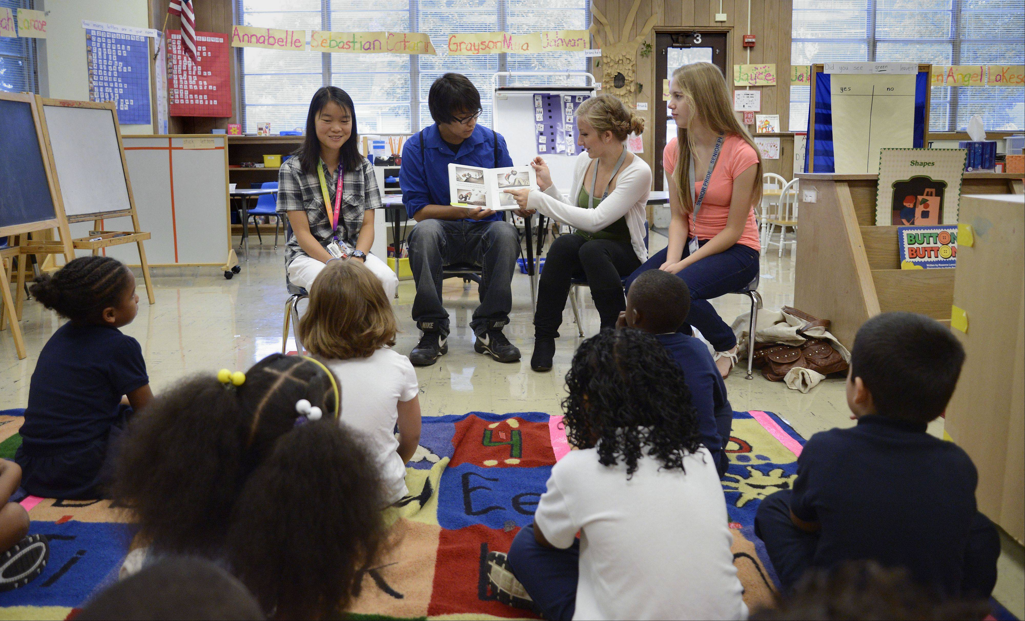 Future Teachers Club members from Elgin's Larkin High School, left to right, Kailin Sepp, Nathaniel Evans, Emily Fischer and Symantha Clough read to kindergartners at Gifford Elementary School in Elgin. Officials of Elgin Area School District U-46 hope some of the diverse student population will return as teachers.