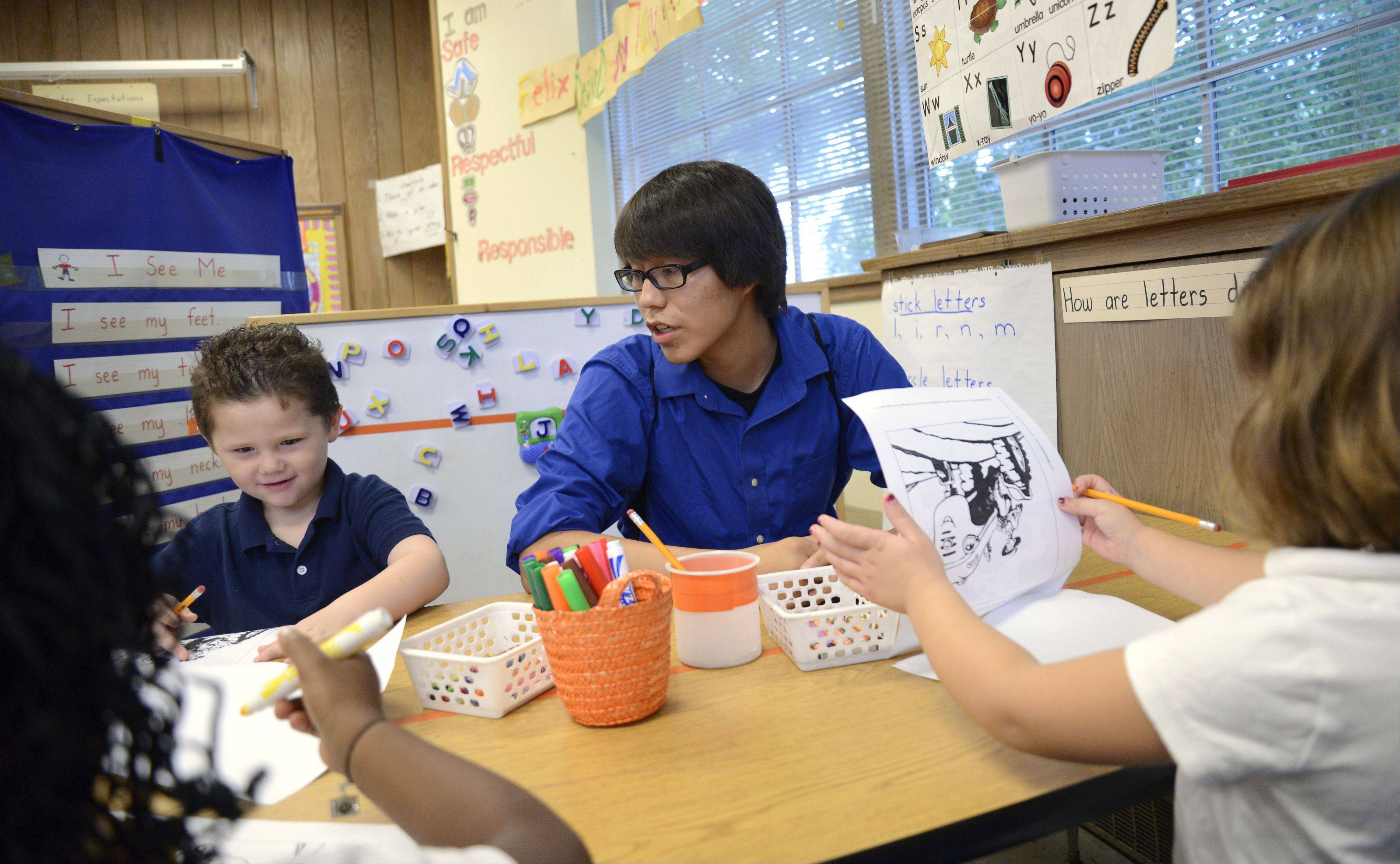 Nathaniel Evans works with Felix Feliciano and other kindergartners at Gifford Elementary School in Elgin. Nathaniel is a member of the Future Teachers Club of Larkin High School.