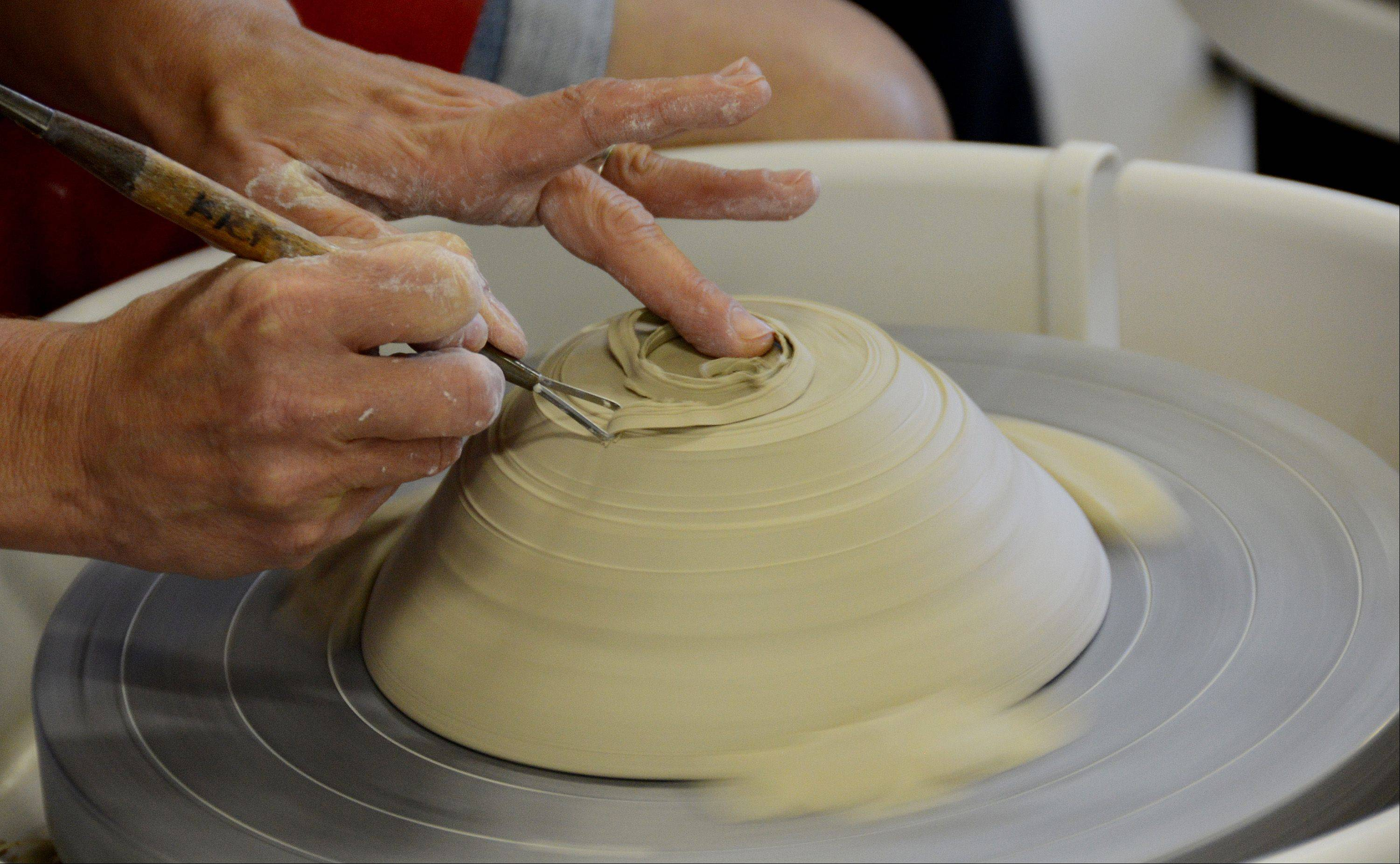 Instructor Linda Kiepke removes excess clay from a spinning bowl. ClaySpace, a nonprofit ceramics studio, has just moved into new facilities in Lisle.
