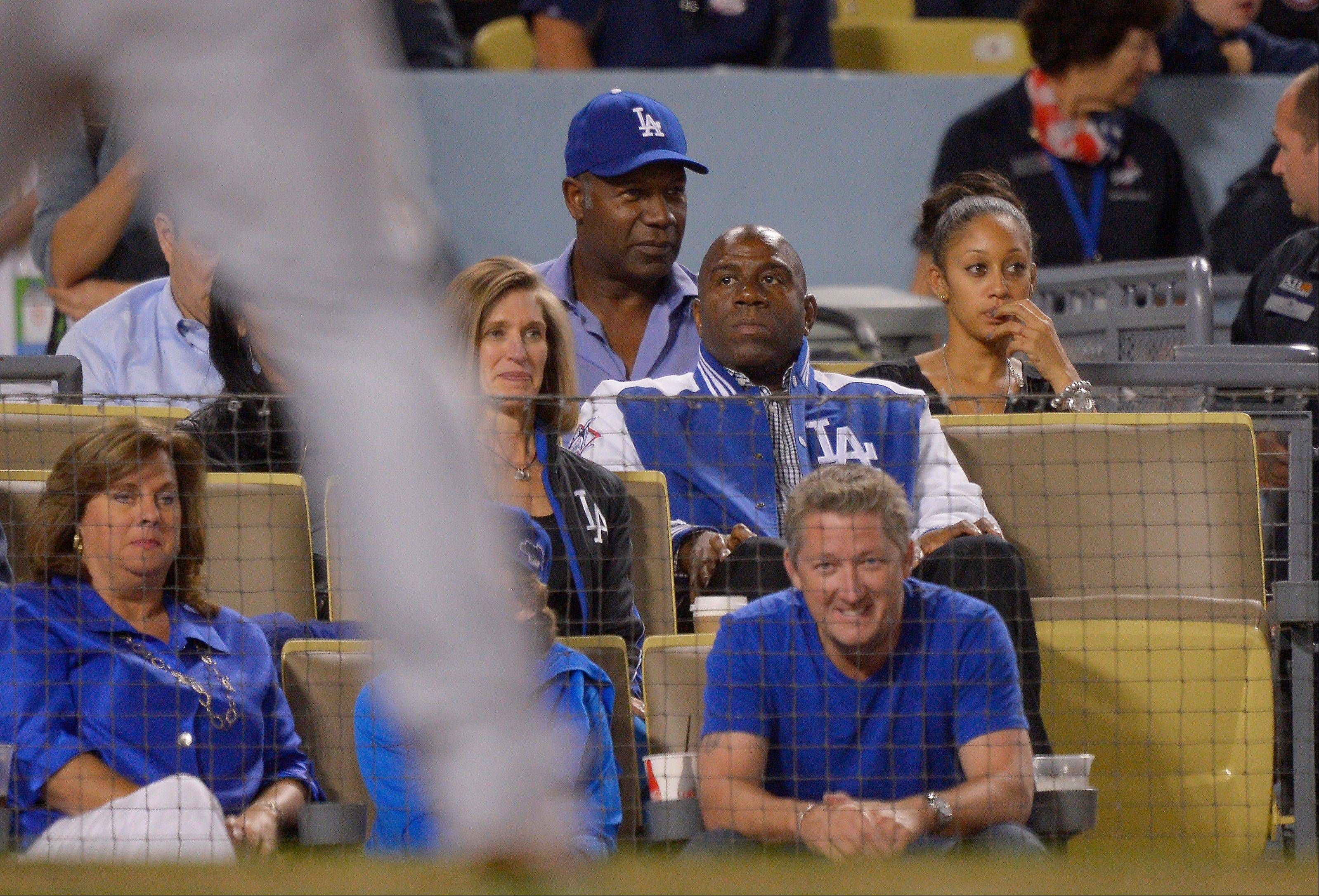 Dodgers owner Magic Johnson, center right, and actor Dennis Haysbert, second from left on top, watch during the sixth inning.