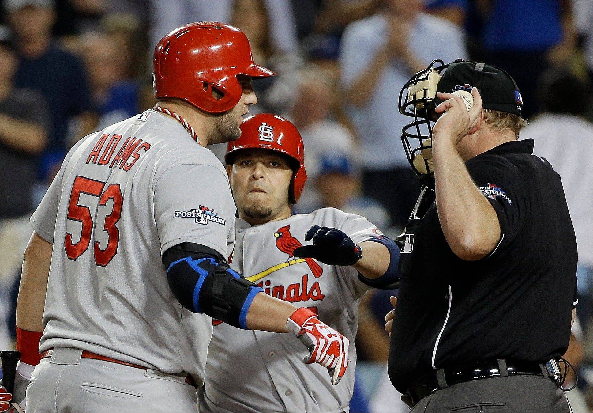 The Cardinals' Matt Adams argues a strike with umpire Bruce Dreckman as teammate Yadier Molina pulls him away during the ninth inning.
