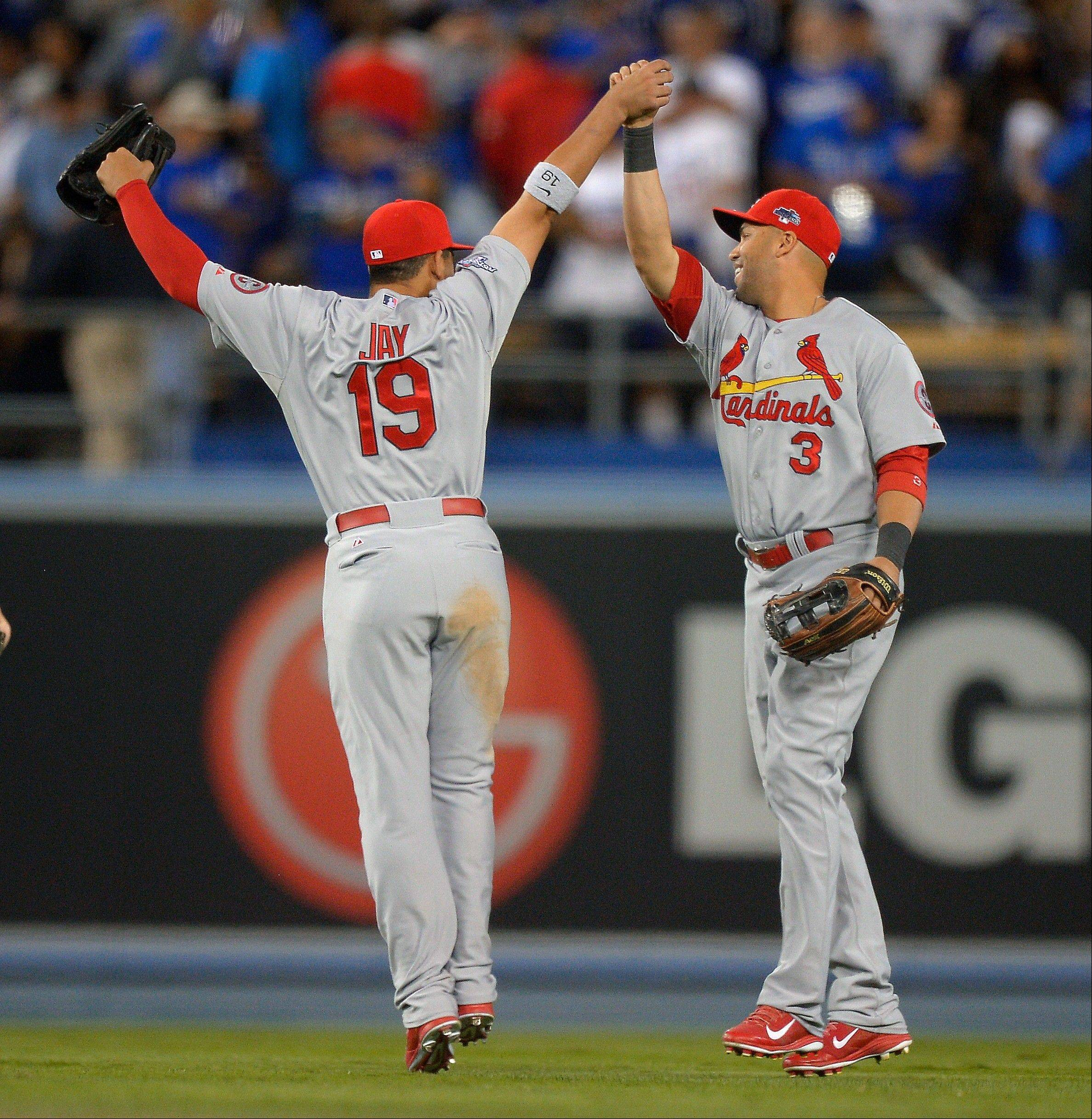 St. Louis Cardinals' Jon Jay and Carlos Beltran, right, celebrate after Game 4 of the National League baseball championship series against the Los Angeles Dodgers Tuesday, Oct. 15, 2013, in Los Angeles. The Cardinals won 4-2 to take a 3-1 lead in the series.