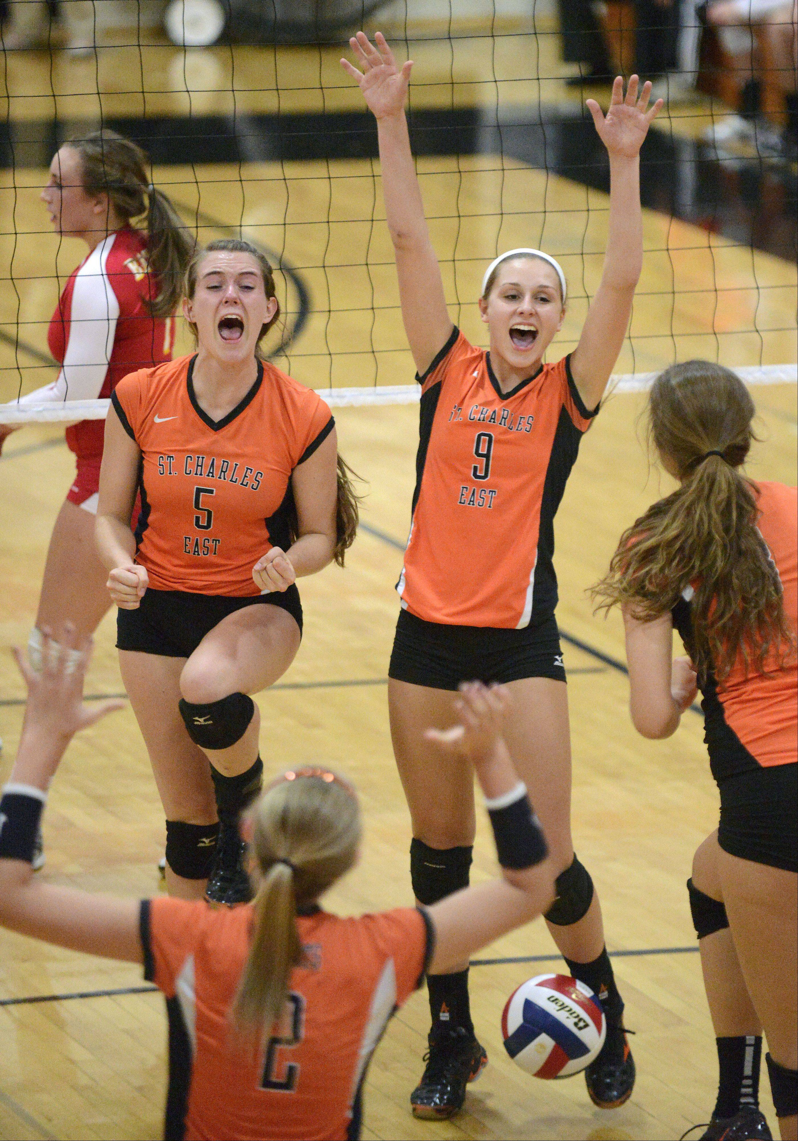 St. Charles East's Alex Mazanke (5) and Megan Schildmeyer (9) celebrate a point over Batavia in the first match on Tuesday, October 14.