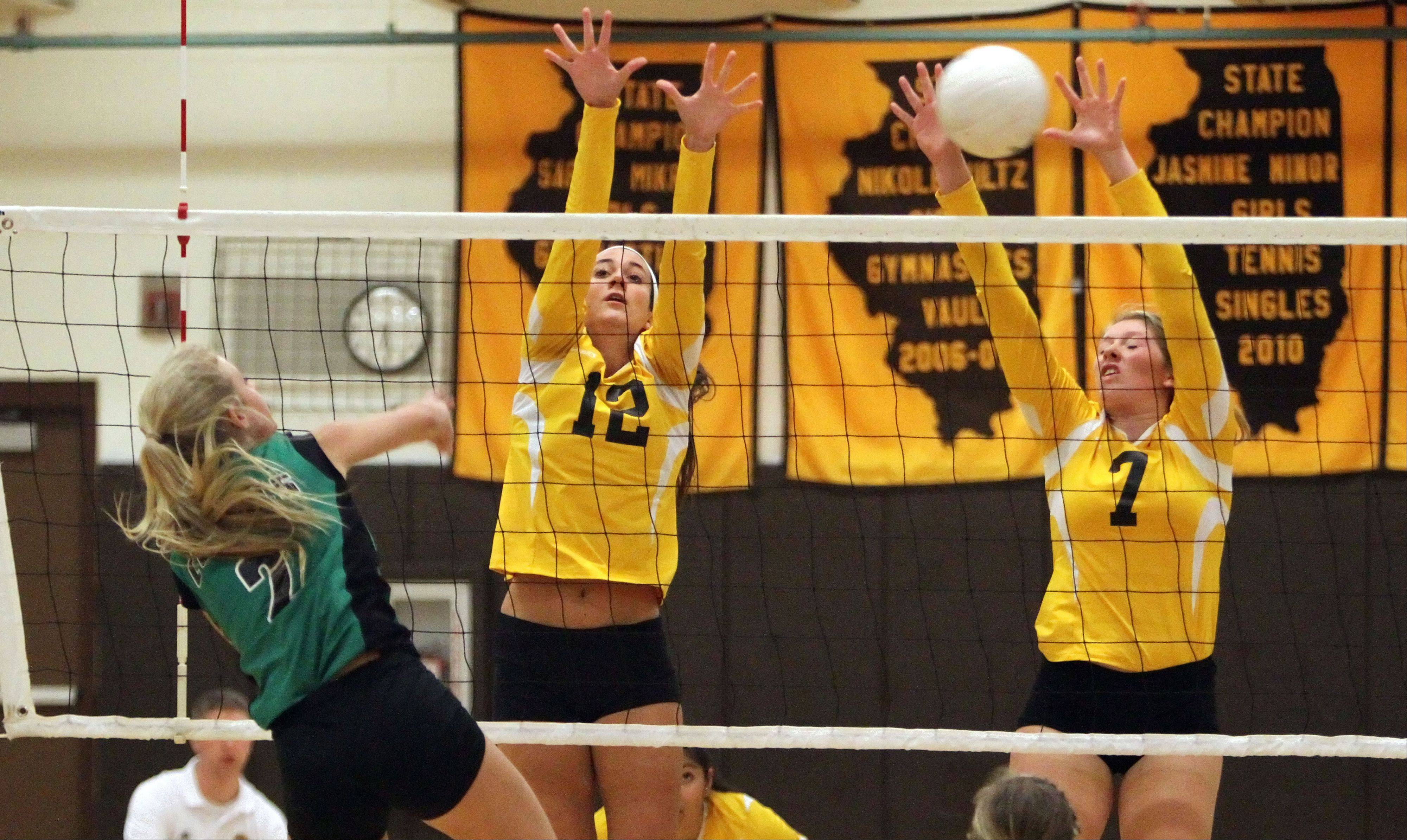 Carmel's Haley Nedelka, left, and Morgan Meade go up to block the shot of Providence Catholic's Clare Urchell on Tuesday night in Mundelein.