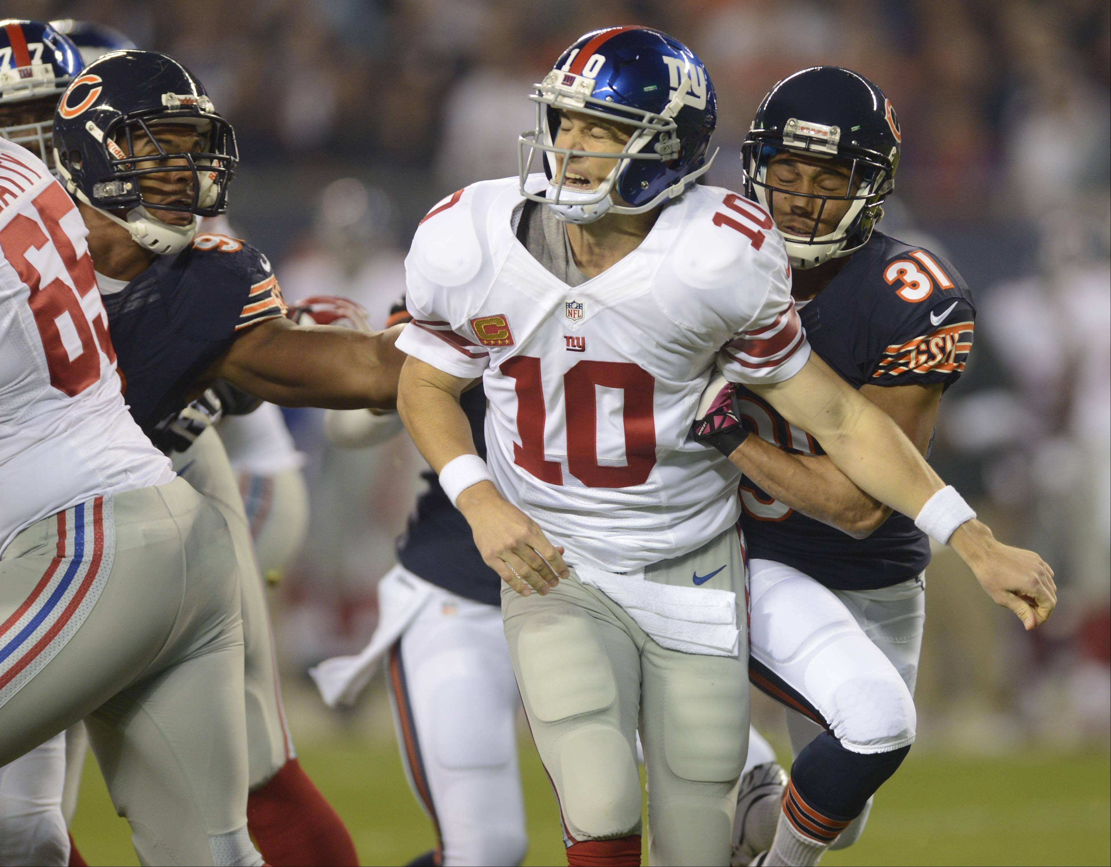 New York Giants quarterback Eli Manning winces as his is hit by Chicago Bears cornerback Isaiah Frey and Corey Wootton Thursday night at Soldier Field in Chicago.