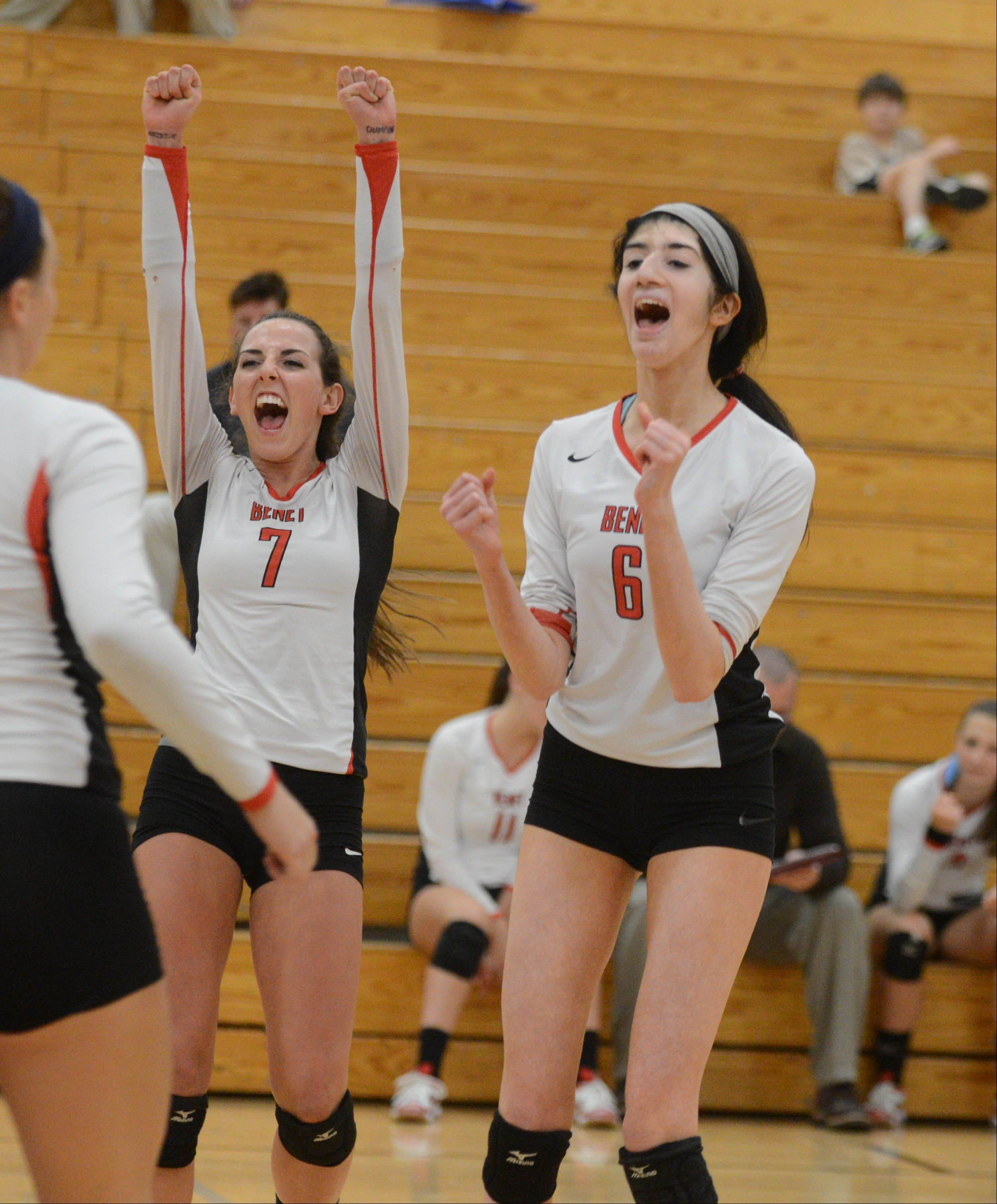 Benet's Whitney Battoe, left, and Stephanie Sinnappan celebrate a point during Thursday's volleyball match against Joliet Catholic.